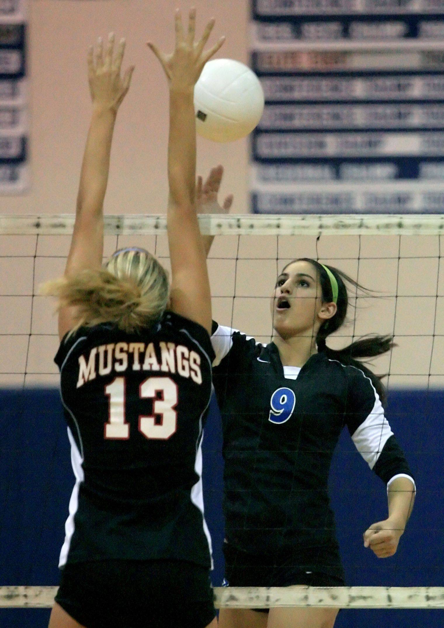 Lake Zurich's Amanda Orchard rises above the net opposite Mundelein's Gina Withrow last season.