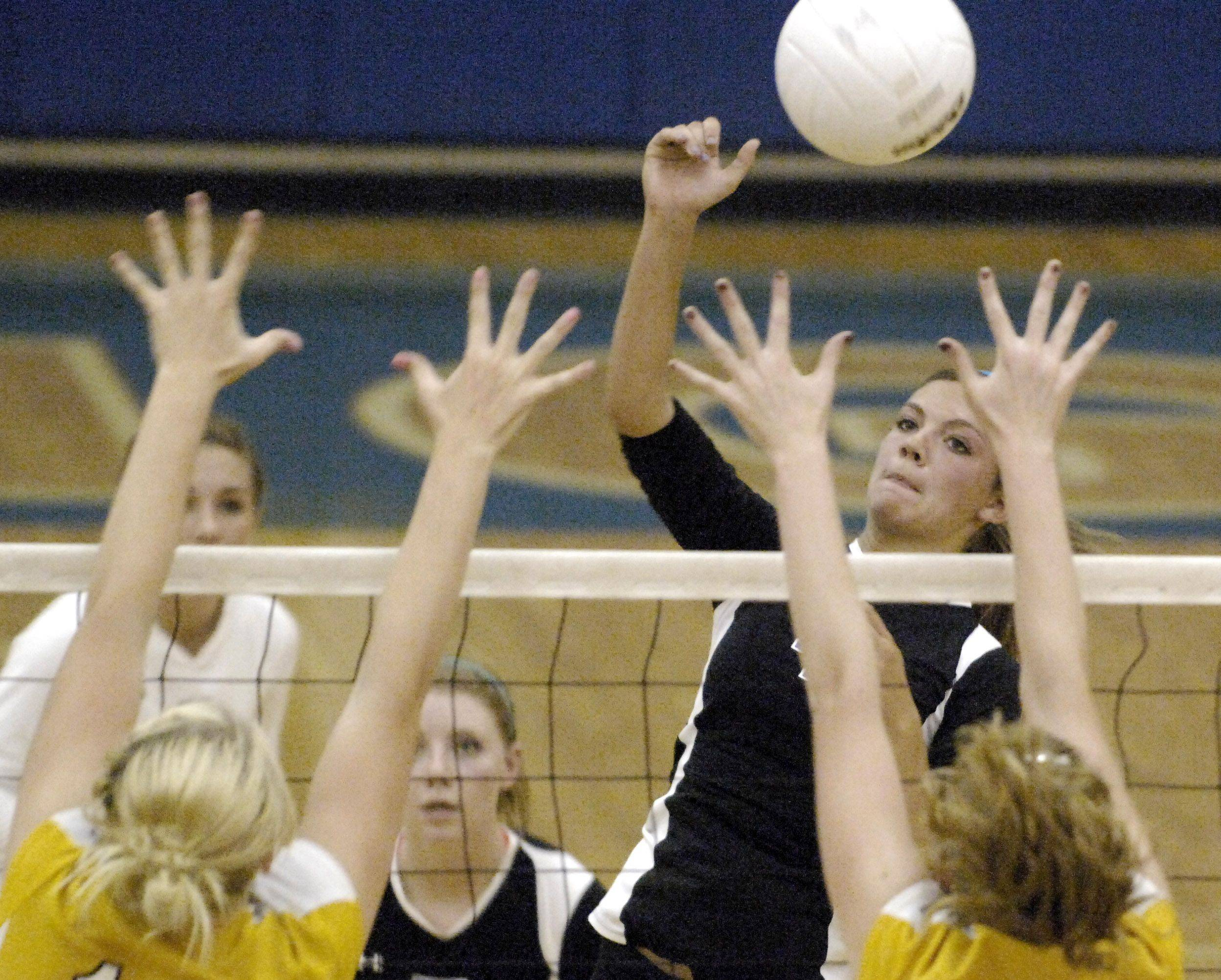 Geneva's Elle Weinstein dinks the ball over a pair of Neuqua Valley blockers during Thursday's game in Geneva.
