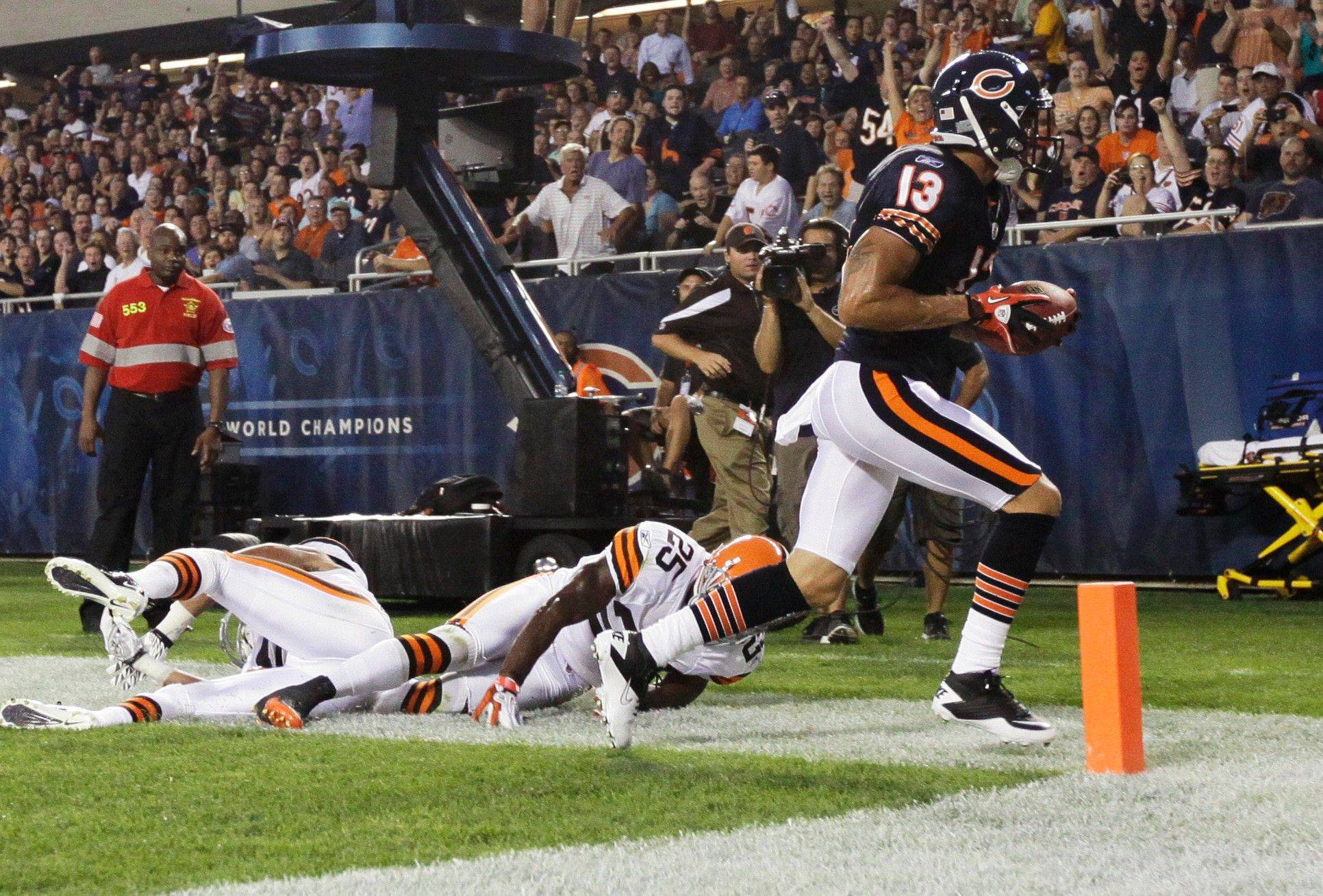 Chicago Bears wide receiver Johnny Knox scores on a pass reception past Cleveland Browns defensive back DeAngelo Smith and another Browns defender in the first half.