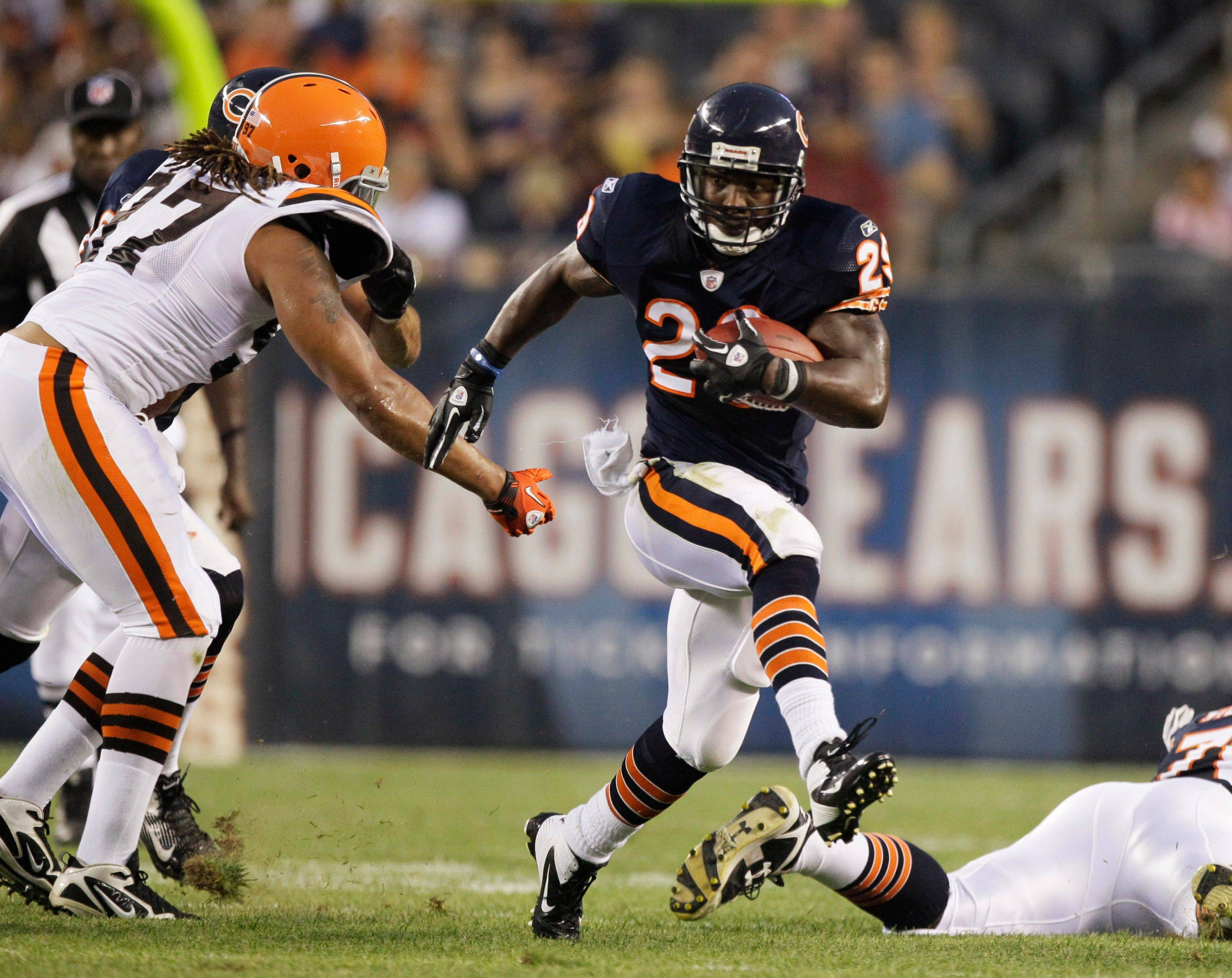 Chicago Bears running back Chester Taylor runs past Cleveland Browns defensive lineman Jabaal Sheard in the first half .