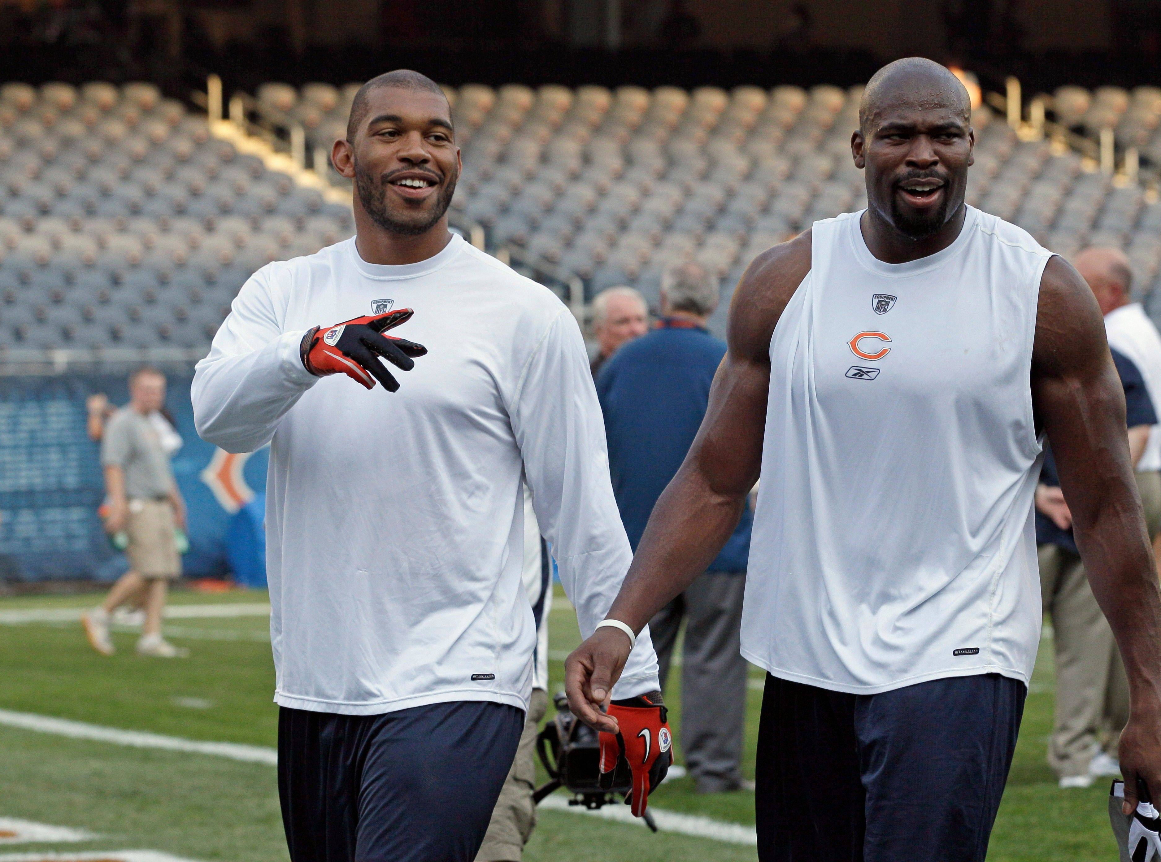 Chicago Bears defensive end Julius Peppers, left, and defensive lineman Israel Idonije walk off the field during warm-ups.