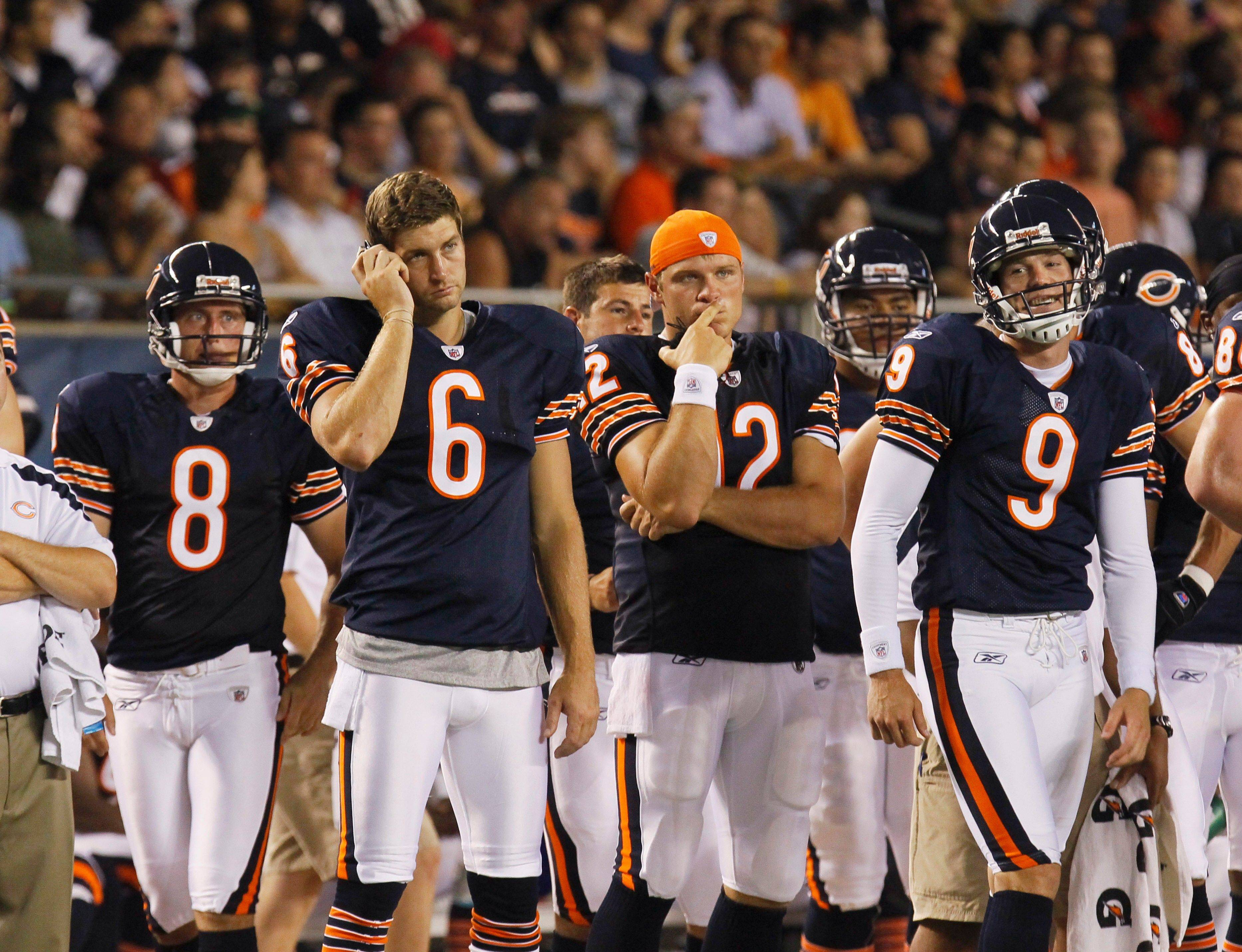 Chicago Bears players punter Adam Podlesh, quarterback Jay Cutler, quarterback Caleb Hanie and placekicker Robbie Gould watch the action from the sidelines in the first half.