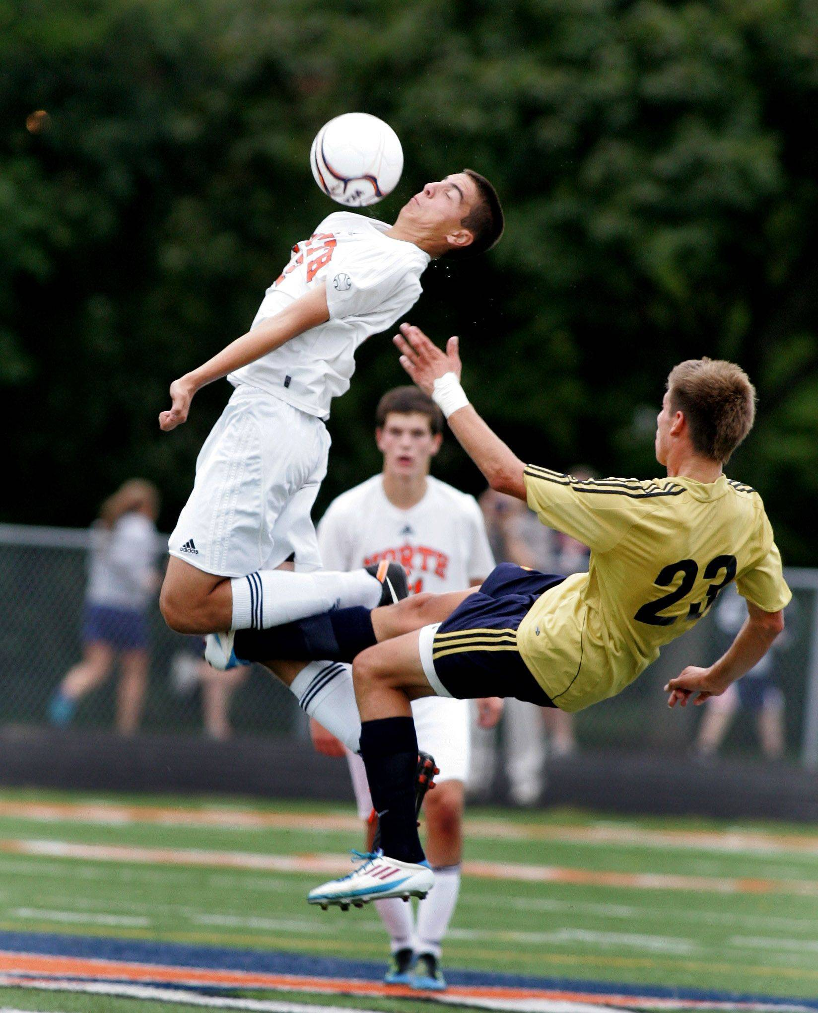 Neil Wiaranowski, left, of Naperville North and Jake Loncar, right, of Neuqua Valley get tripped up in boys soccer action Tuesday in Naperville.