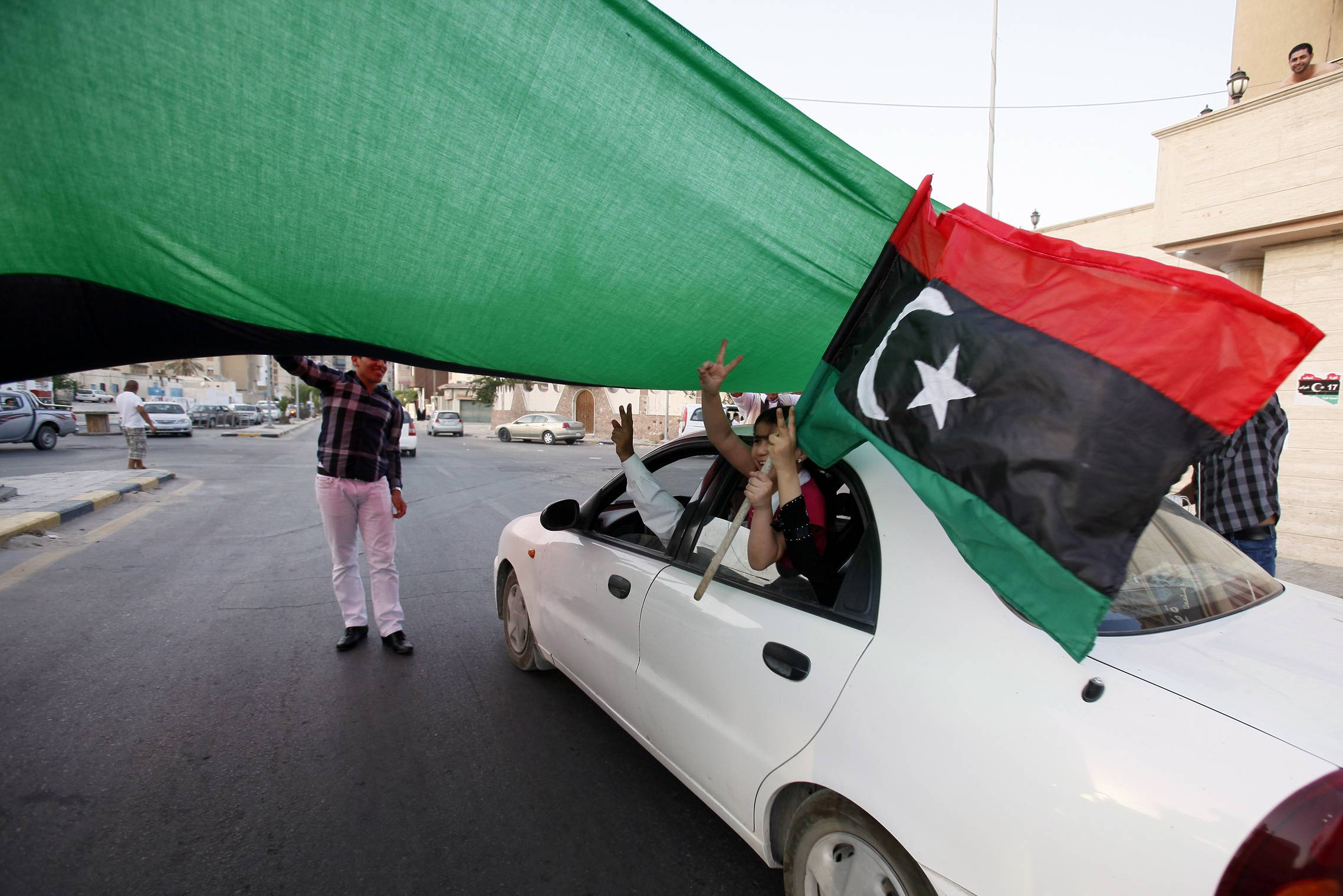 A Libyan girl waves the former Libyan flag from a car driving under a giant flag in the street of Jamal Goubtan district inTripoli, Libya, Thursday. A TV station is quoting Moammar Gadhafi as warning that tribes loyal to him in key strongholds are armed and won't surrender to Libyan rebels. Thursday's report on Syrian-based Al-Rai TV comes as the rebels who have seized control of most of the country extended by a week a deadline for the surrender of Gadhafi's hometown of Sirte - originally set for Saturday.