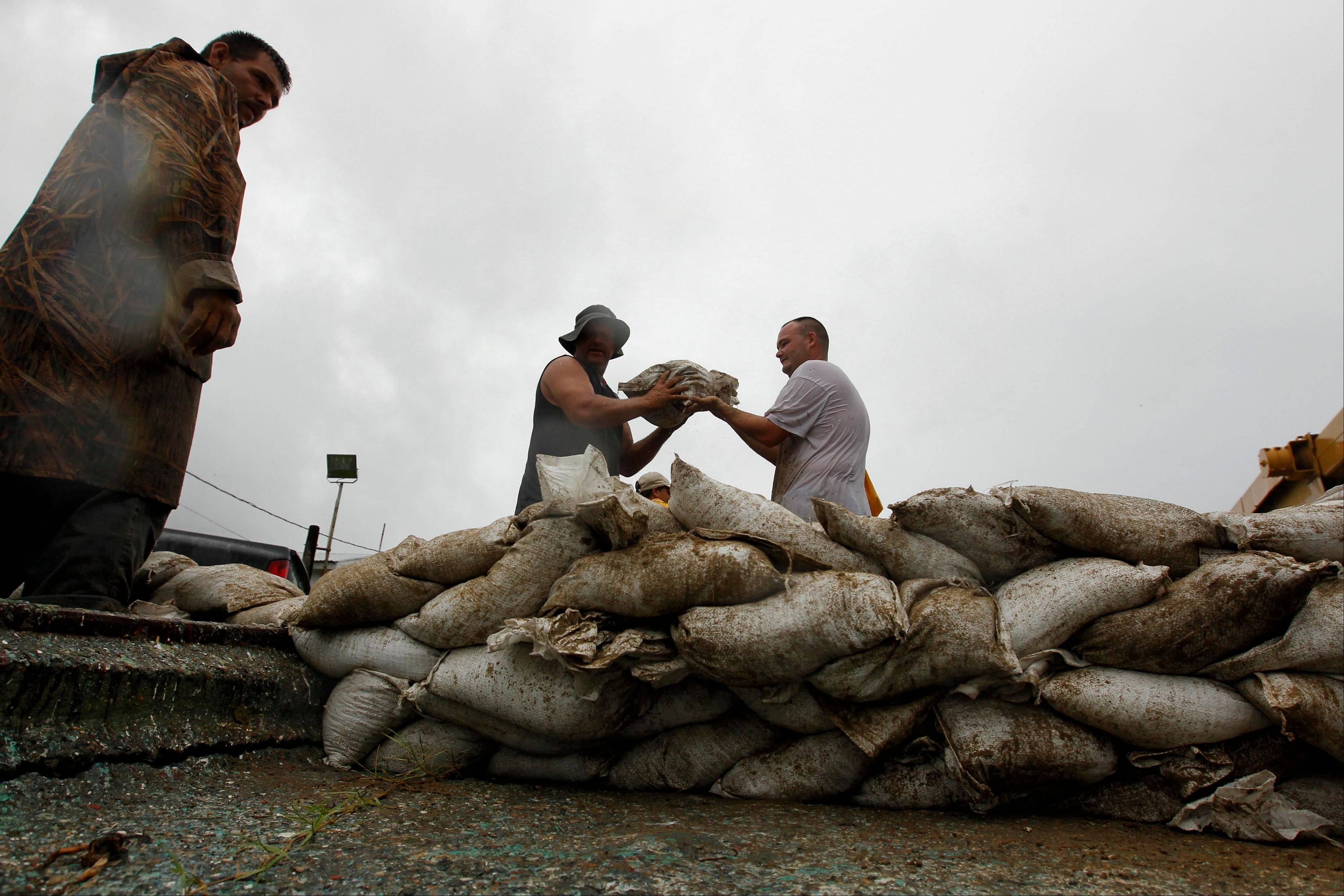 Residents help sandbag a seafood shed behind the home of resident Kraemer Lloyd, in preparation for encroaching Tropical Storm Lee, in the town of Jean Lafitte, La., Friday. Tropical Storm Lee formed in the waters off Louisiana on Friday, threatening a drenching along much of the Gulf Coast over the Labor Day weekend with up to 20 inches of rain in some spots.