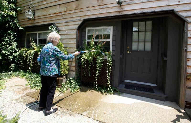 Jane Merrill Waters Flowers Outside Of Her Apartment In The Home Son William