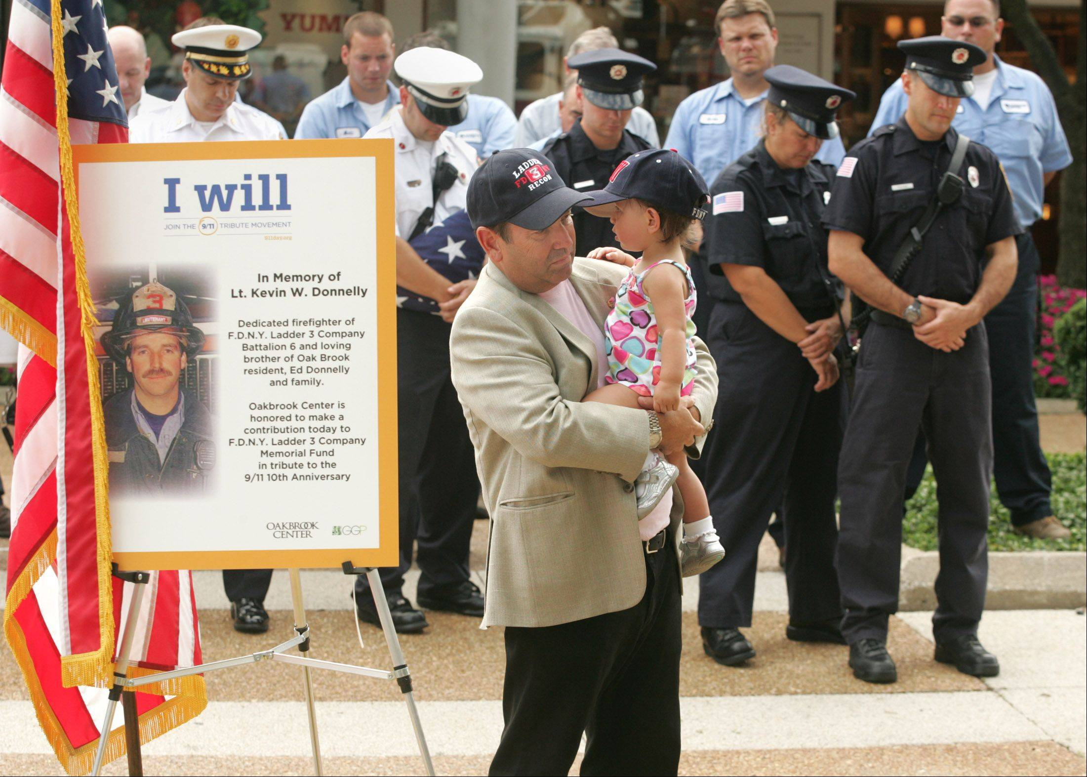 Oak Brook resident Ed Donnelly holds his granddaughter Olivia during a moment of silence Friday for his brother, fire Lt. Kevin W. Donnelly, who was killed in the Sept. 11, 2001, terrorist attacks at the World Trade Center in New York City.