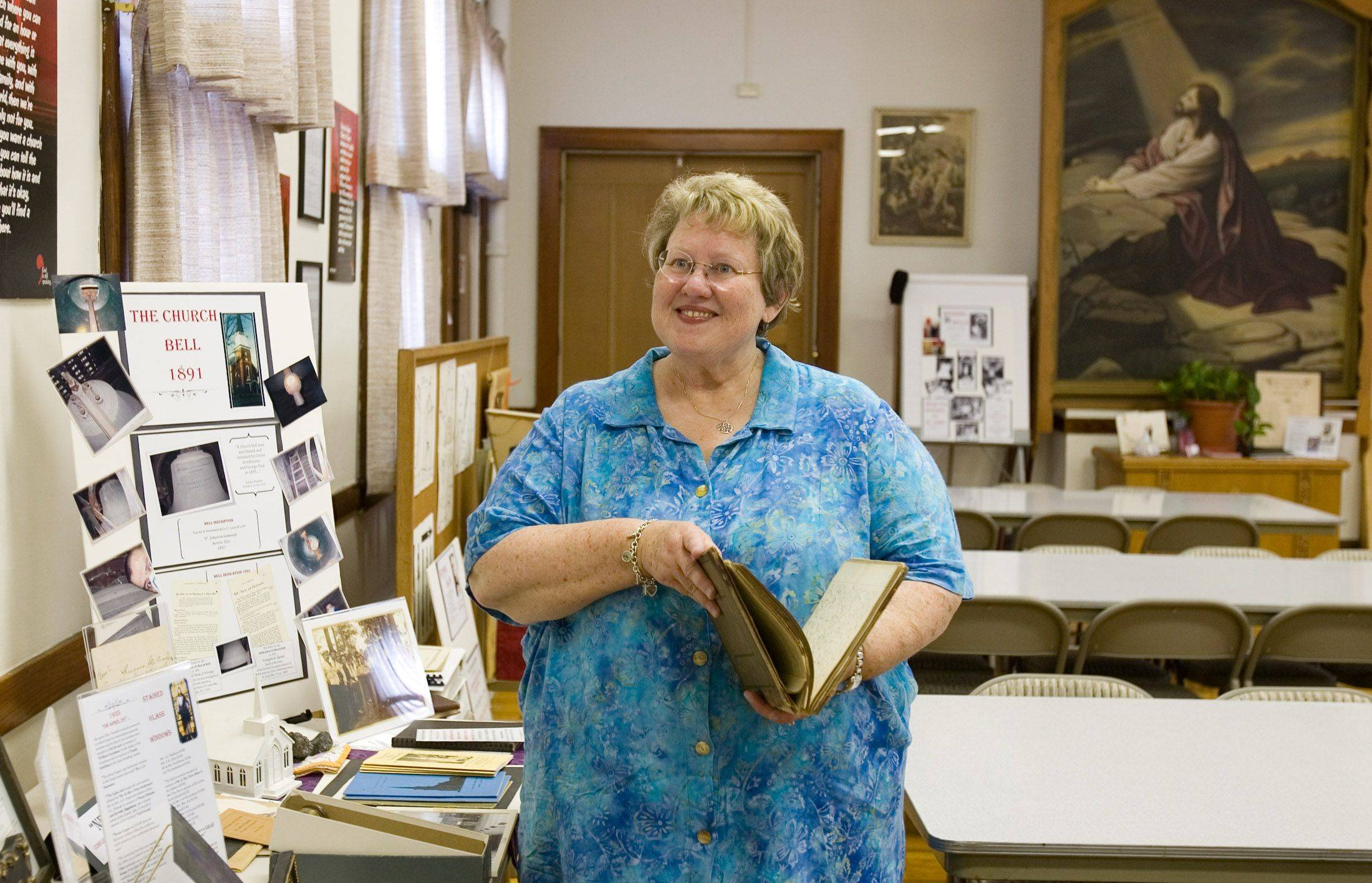 The Rev. Cyndi Gavin, pastor at St. John United Church of Christ in Aurora thumbs through the church�s original constitution and minutes beginning when the church was established in 1886 and lasting until 1915.