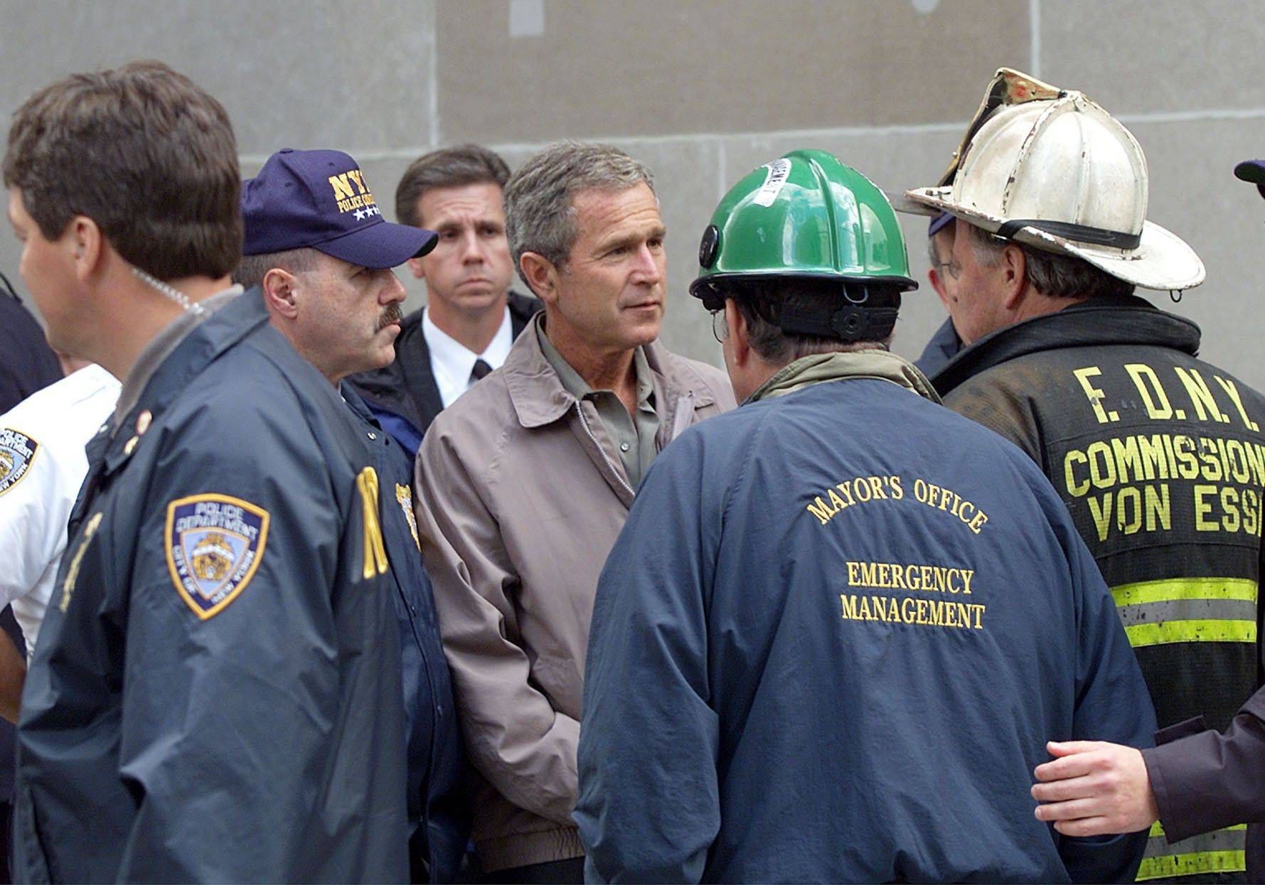 President George W. Bush talks to former New York City Fire Commissioner Thomas Van Essen, right, wearing helmet, during a tour of the World Trade Center in New York.