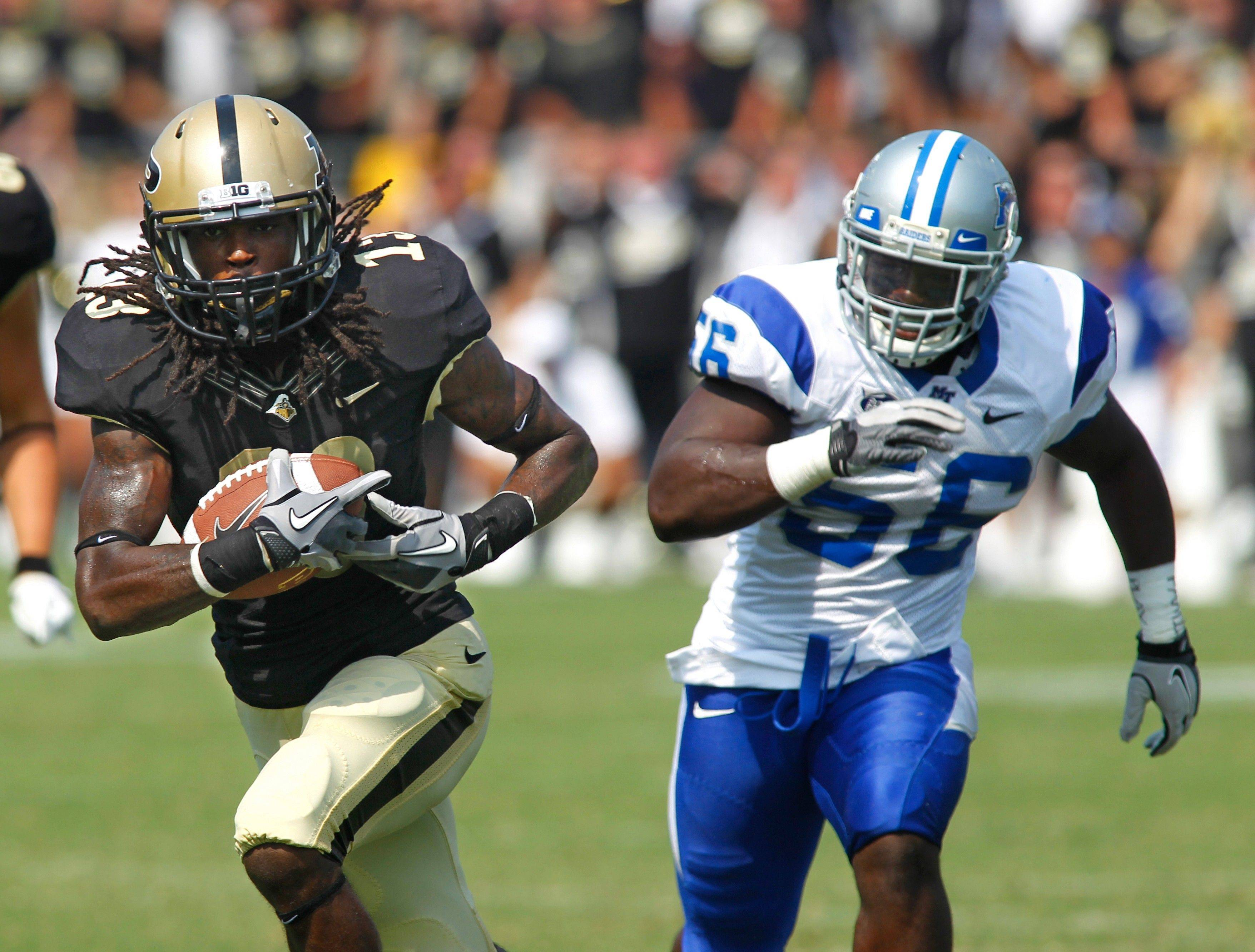 Purdue�s Antavian Edison, left, runs away from Middle Tennessee�s Norman Washington to score the game-winning touchdown late in the fourth quarter Saturday.