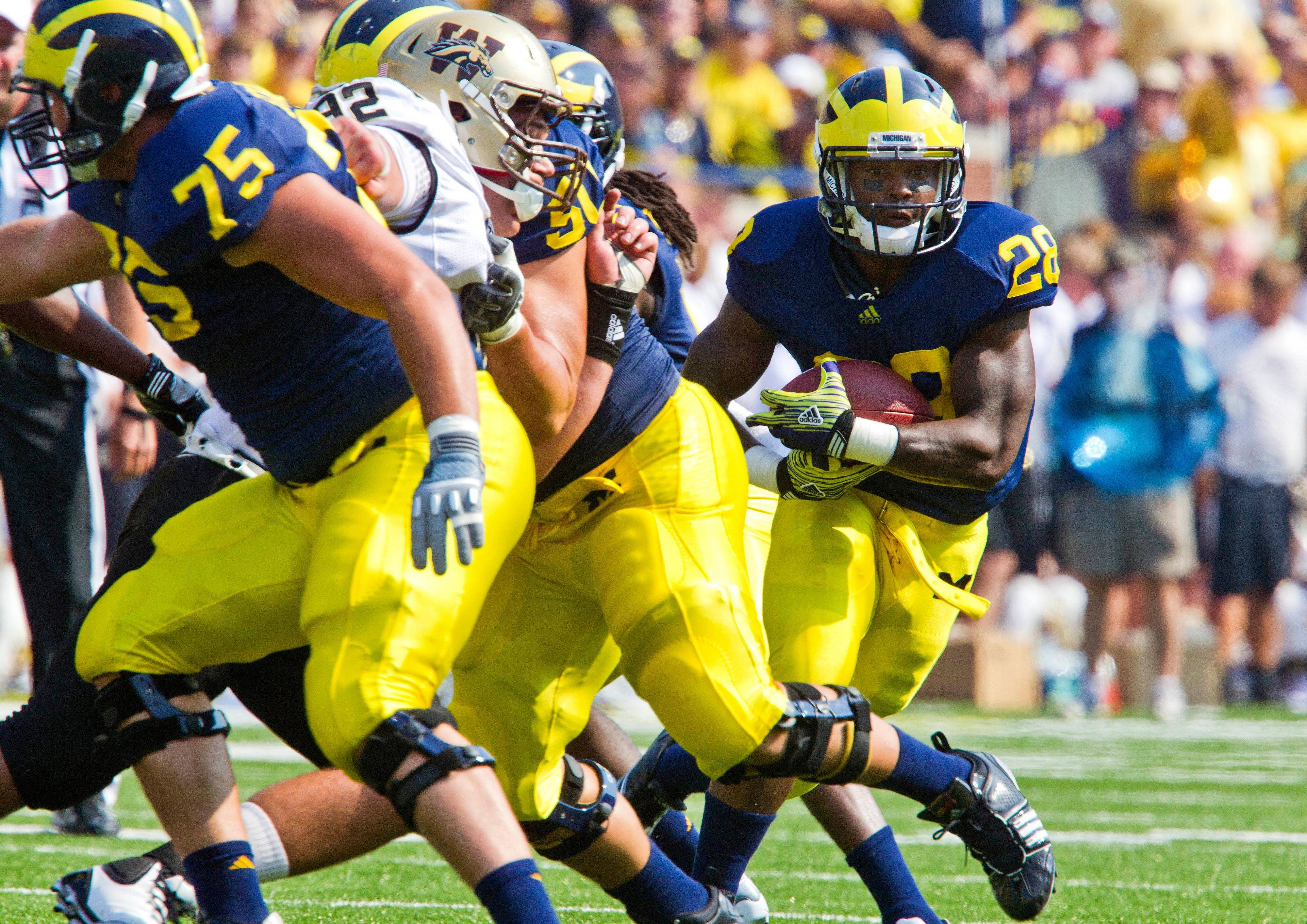 Michigan running back Fitzgerald Toussaint breaks away from the pocket after taking a handoff in the first quarter Saturday.