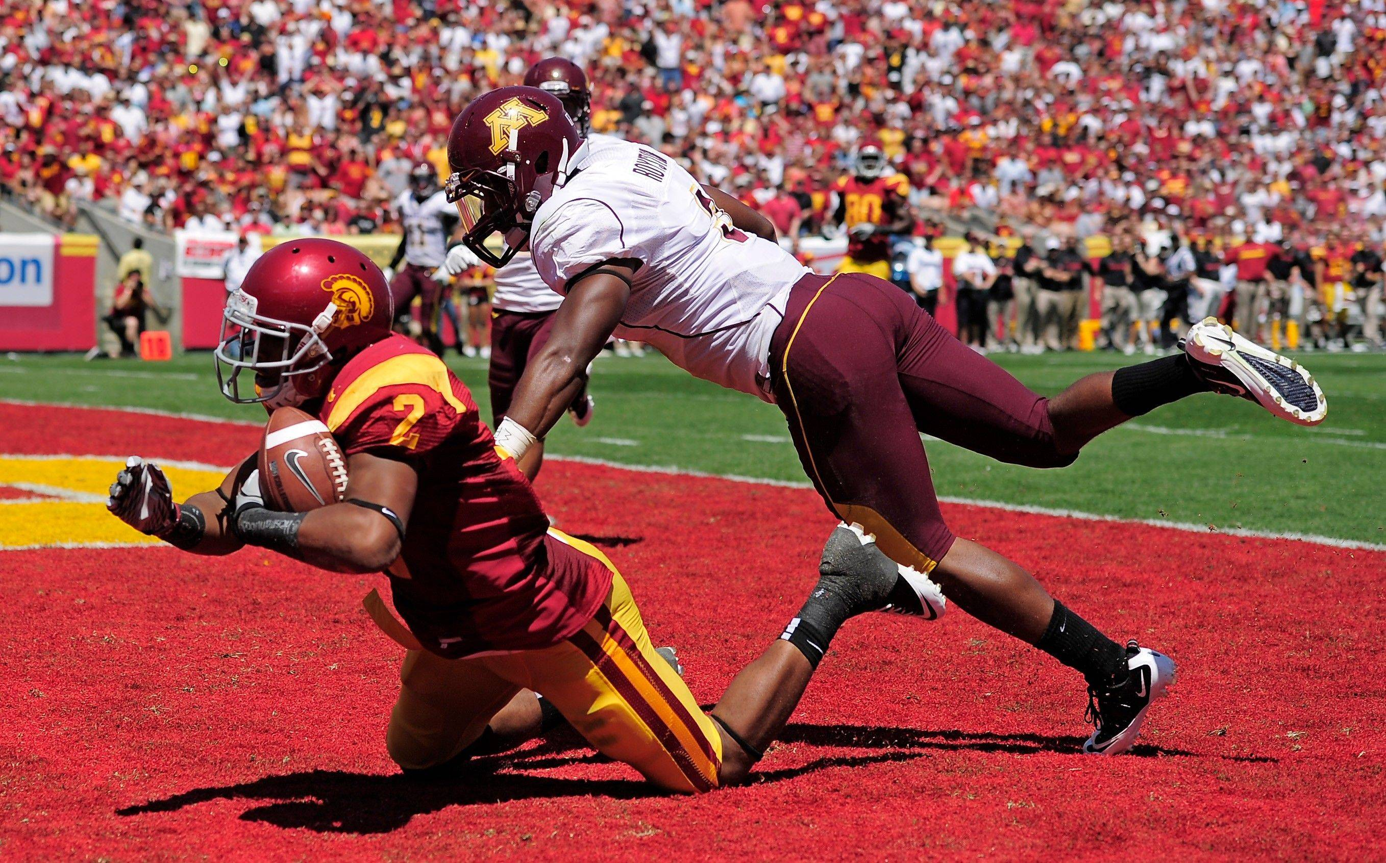 Southern California wide receiver Robert Woods catches a touchdown pass as Minnesota defensive back Kim Royston defends during the first half Saturday.