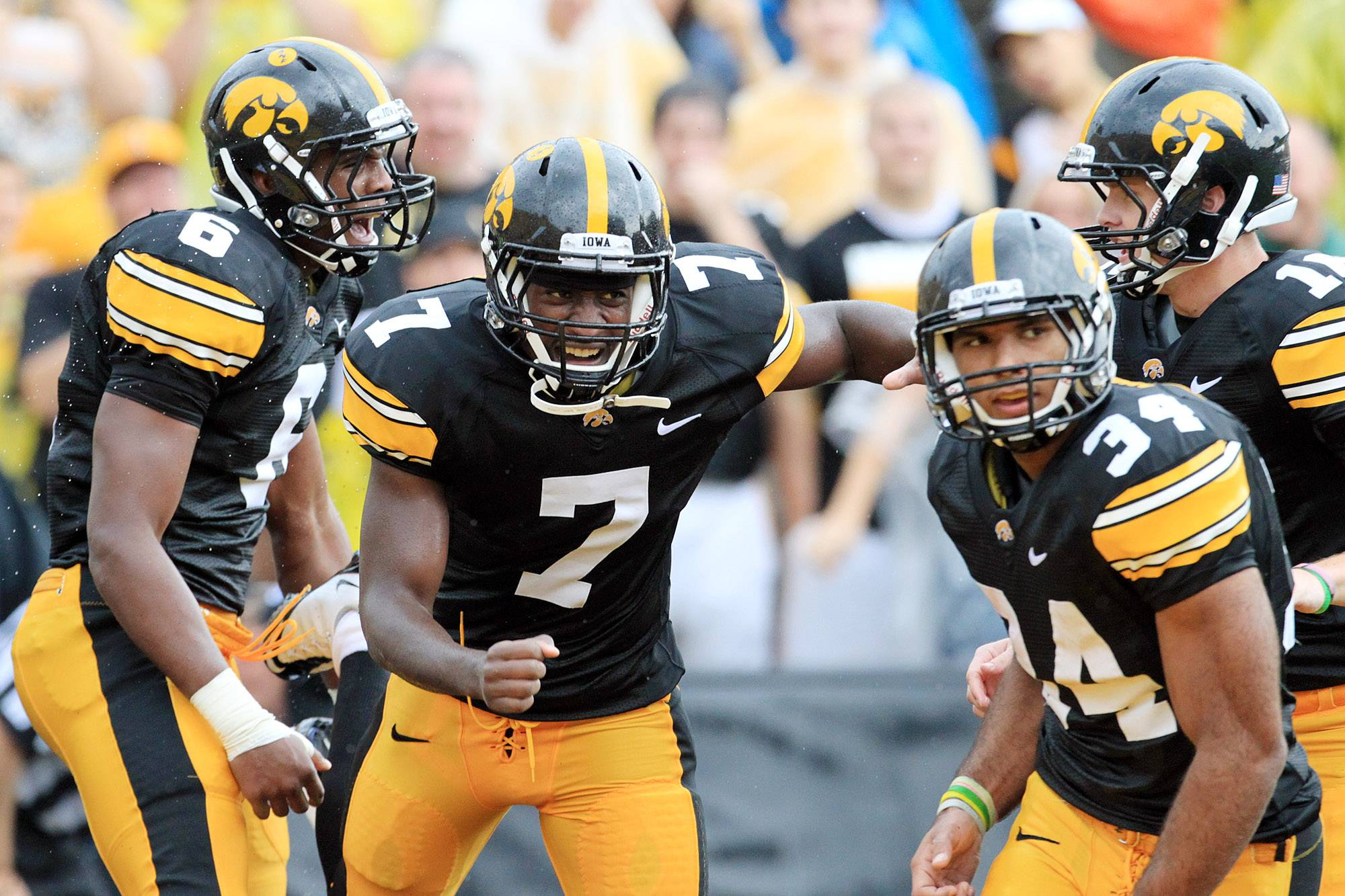 Iowa's Keenan Davis (6,), Marvin McNutt, Jr. (7), Marcus Coker (34) and James Vandenberg (16) celebrate after a long reception by Davis in the second quarter Saturday.
