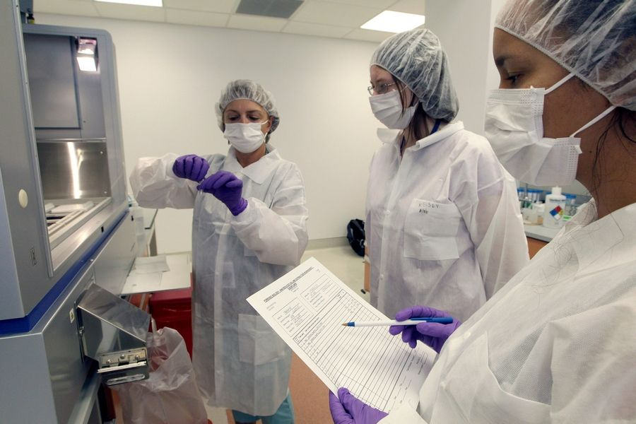 Tatyana Gryazeva, left, instructs Lache Rossouw, right, a visiting scientist from South Africa, and Kelsey Baker, an intern, on extracting DNA at a training lab in New York.