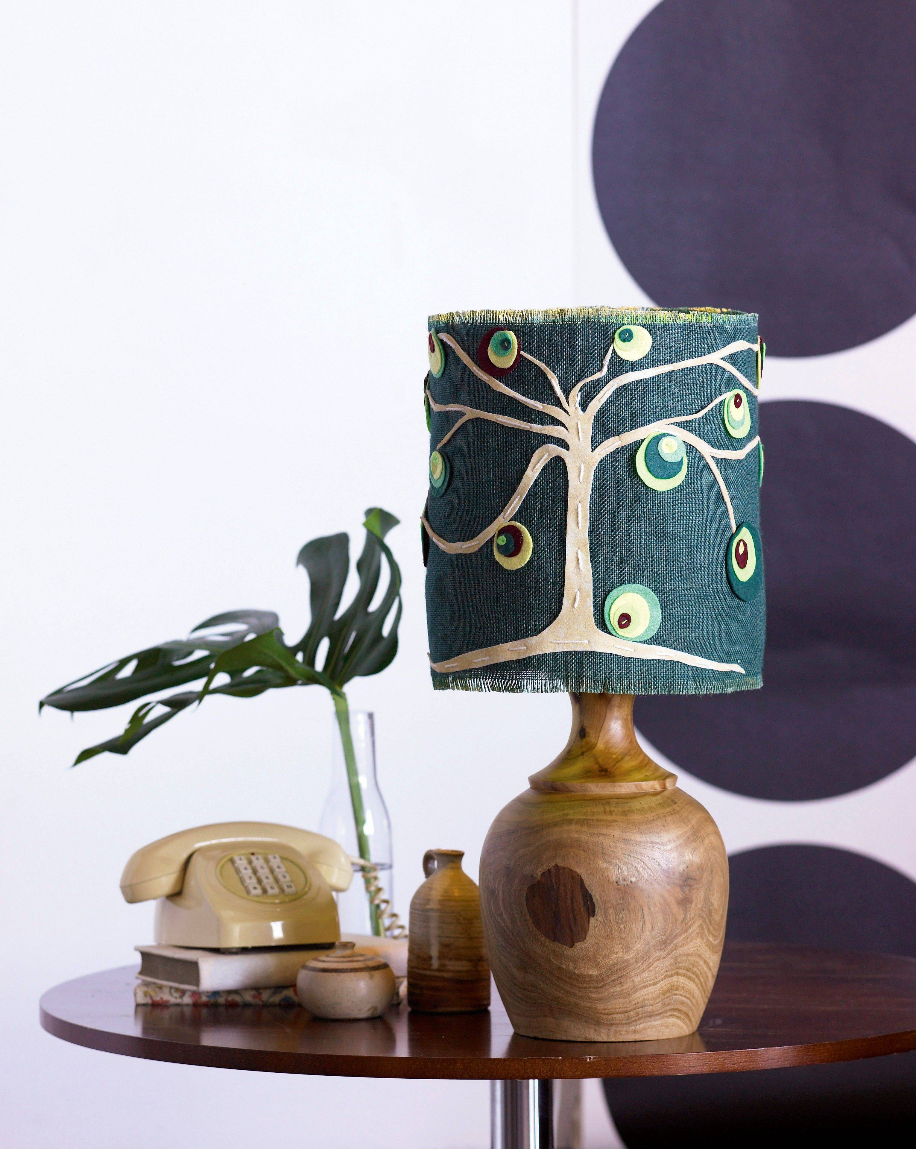 Update an old lamp by simply covering the shade with a DIY design. Colored burlap embellished with a felt design is attached to the lamp's existing shade with spray adhesive.