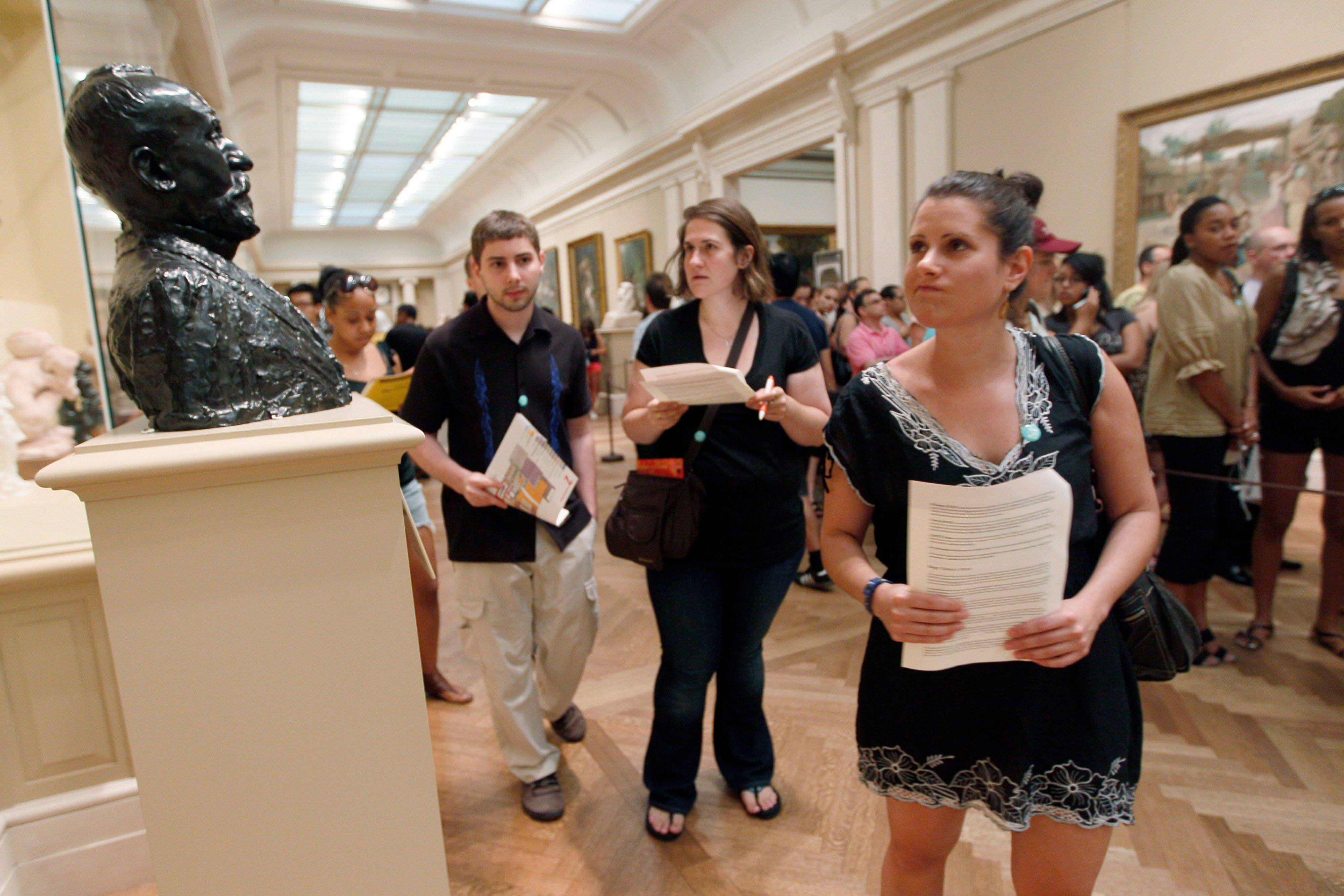 "Matthew Meche, left, Dana Zolli and Noga Pnueli compare notes in one of the galleries at the Metropolitan Museum of Art during a ""Murder at the Met"" scavenger hunt."