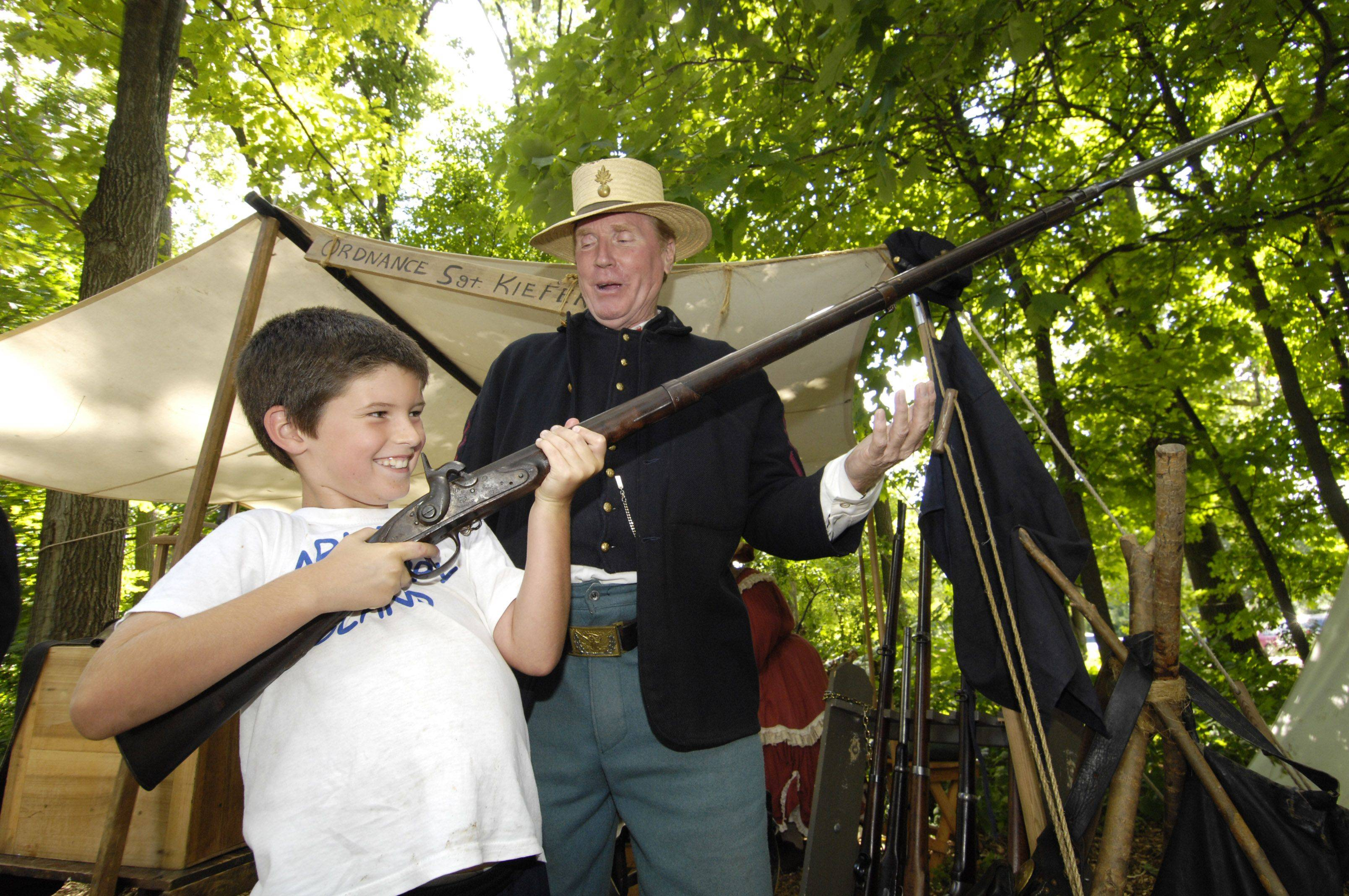 Jack Sullivan, 8, of Chicago holds a model 1795 Springfield rifle as he talks with Civil War re-enactor Pete Kiefert of Coal City. A Civil War Encampment was set up at the Graue Mill and Museum in Oak Brook this weekend, on the 150th anniversary of the war.