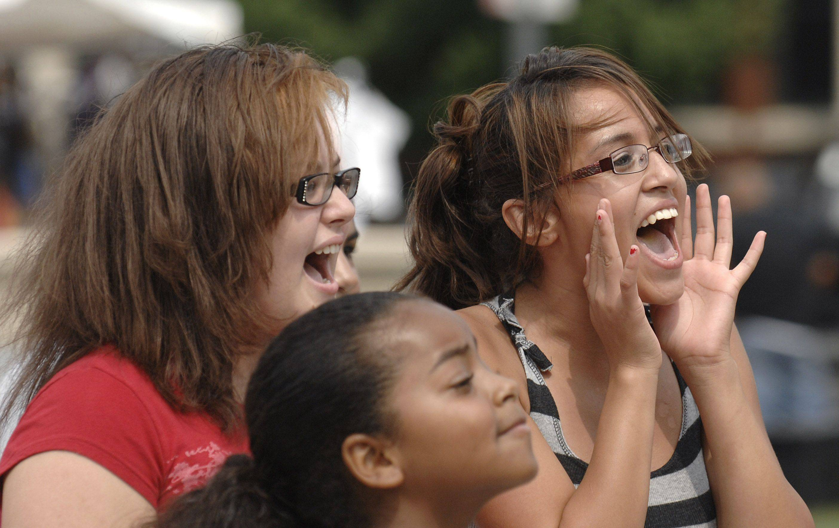 Mariyanna Santiago, left, and Aryana Cintora, both 14 and from Elgin, sing along as the Ragdoll Rock Band performs Saturday at Fiesta Salsa in Elgin.