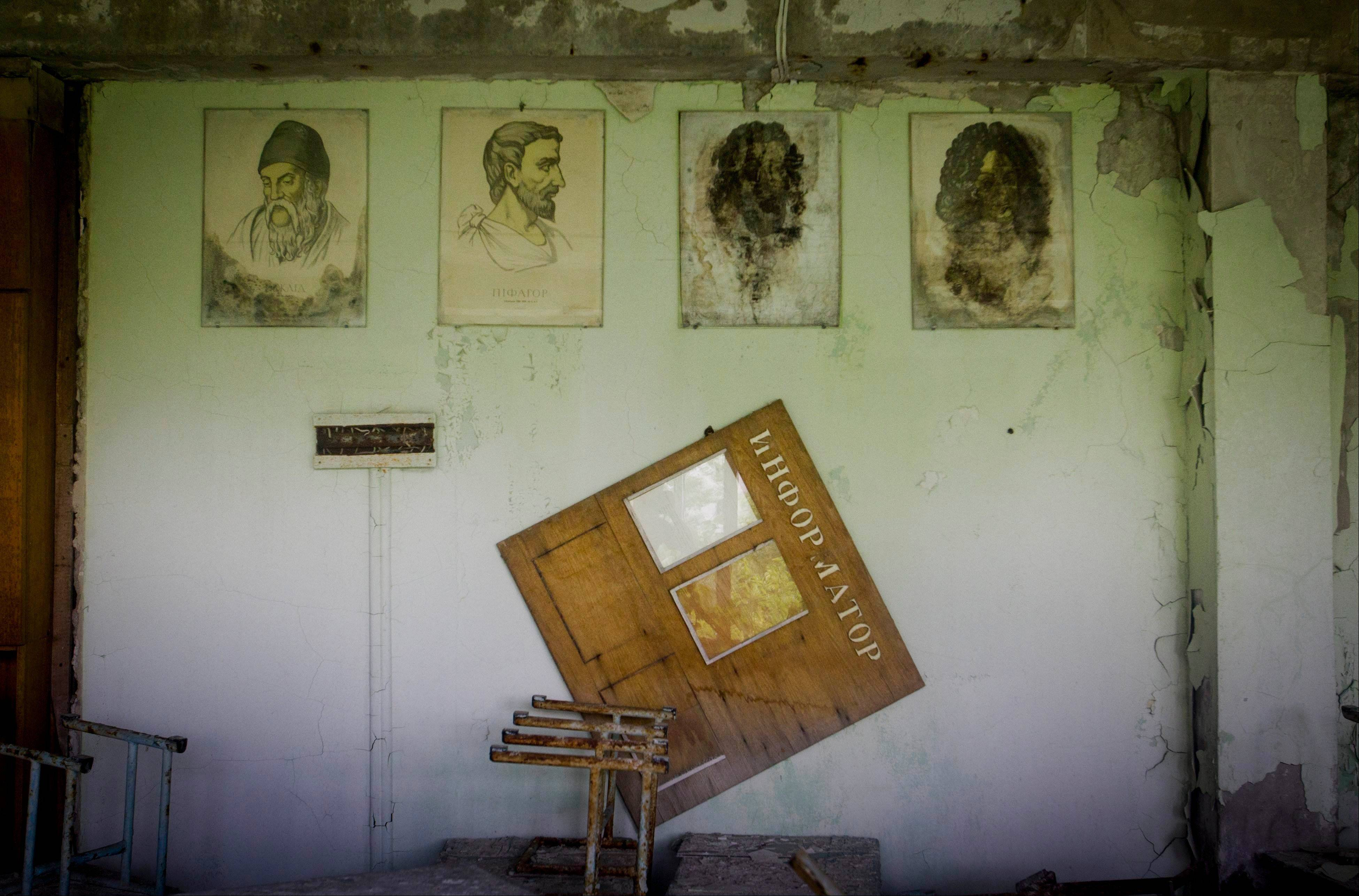 In this Wednesday, June 8, 2011 photo, portraits of ancient physicists and mathematicians hang on a wall in a school in the deserted town of Pripyat, Ukraine, some 3 kilometers (1.86 miles) from the Chernobyl nuclear plant. Chernobyl and Fukushima are some 5,000 miles apart but have much in common. The towns nearest to each of these stricken nuclear power stations, in Ukraine and Japan, whose disasters struck 25 years apart, already reveal eerie similarities.