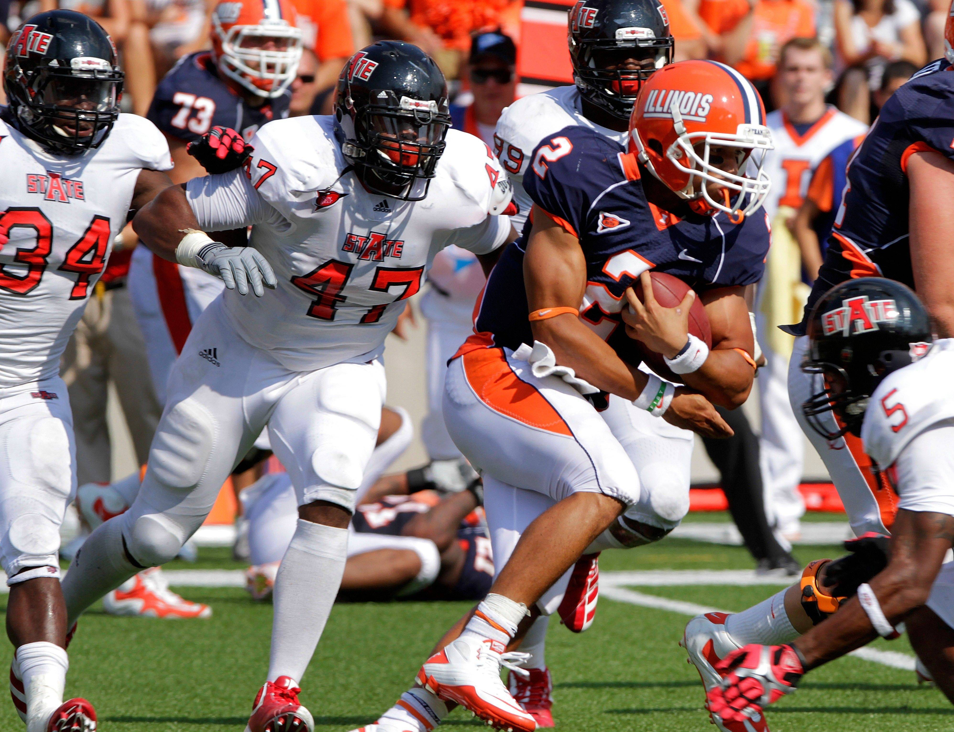 Illinois quarterback Nathan Scheelhaase is surrounded by Arkansas State defensivemen as he runs out of the pocket during the first half Saturday.