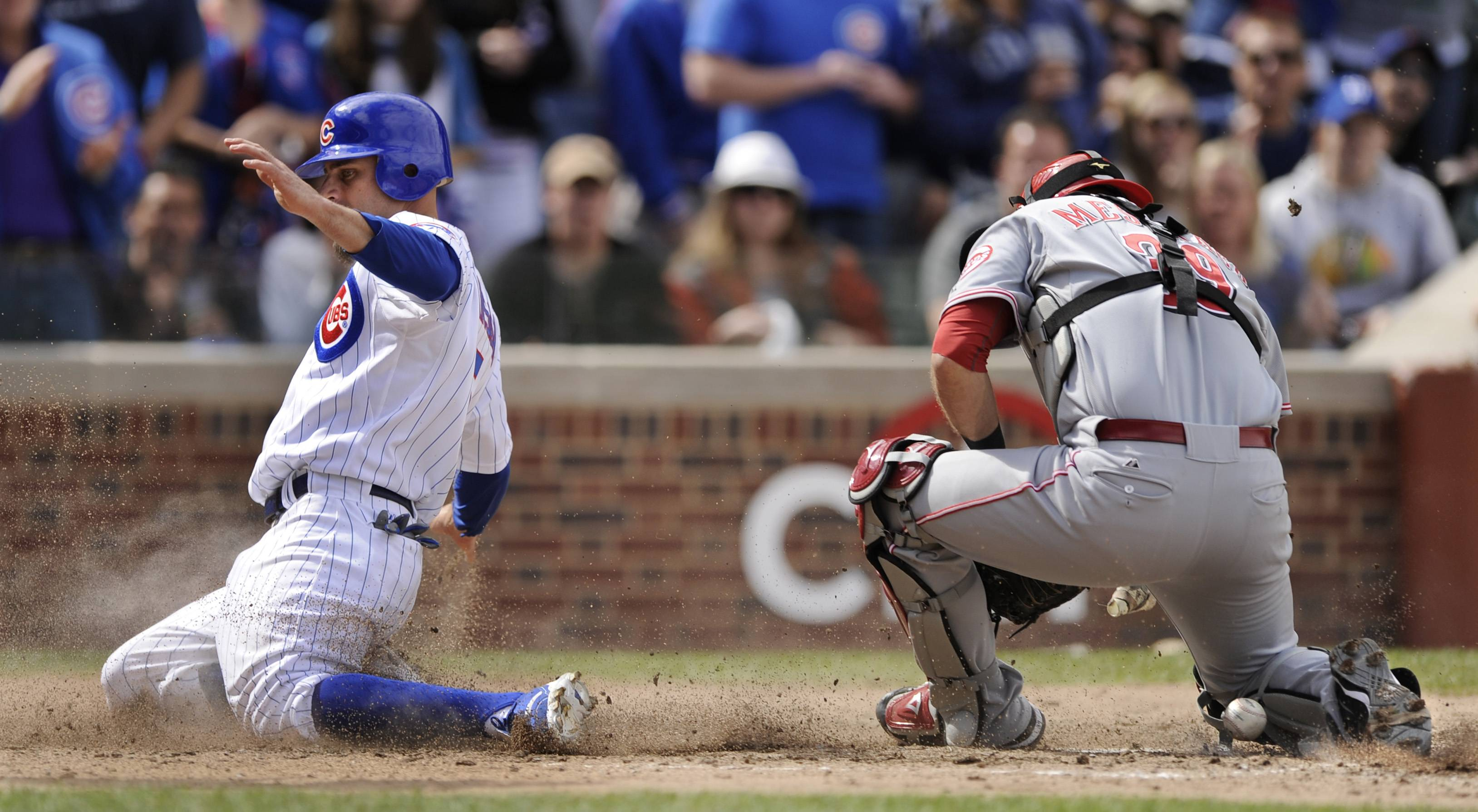 Chicago Cubs' Reed Johnson, left, slides into home plate safely as Cincinnati Reds catcher Devin Mersoraco drops the ball during the fifth inning Monday in Chicago.