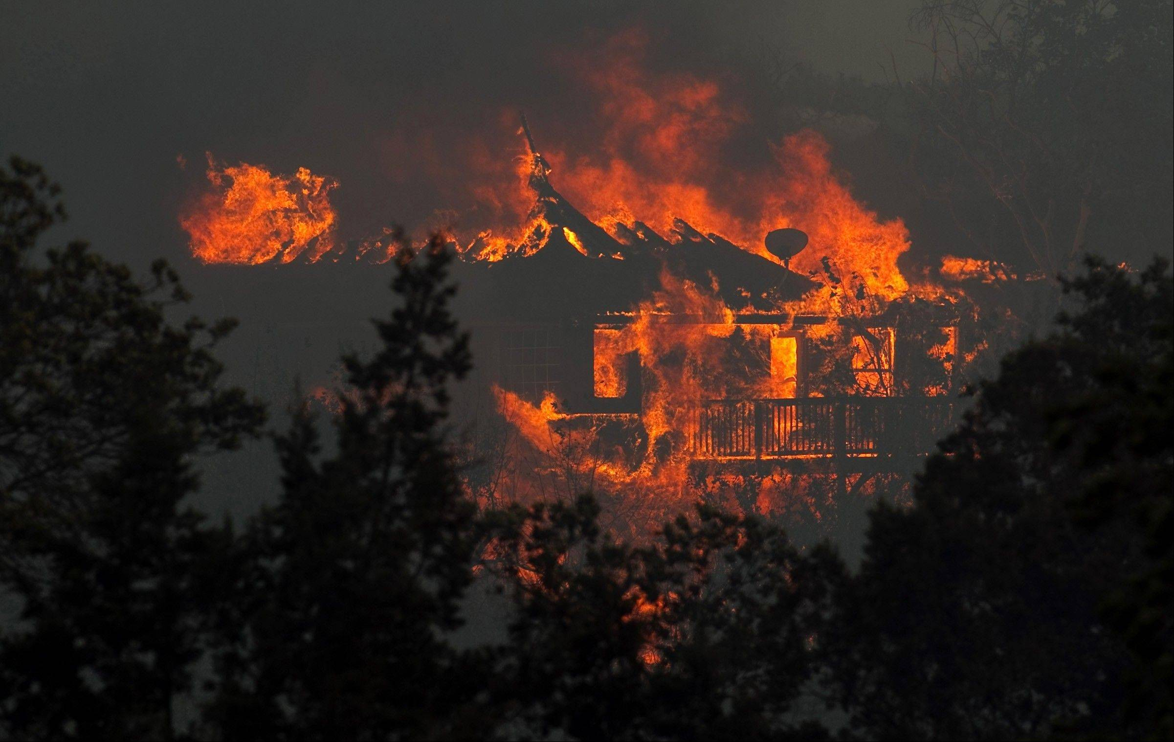 A fire burns a home in Steiner Ranch west of Austin, Texas, Sunday.