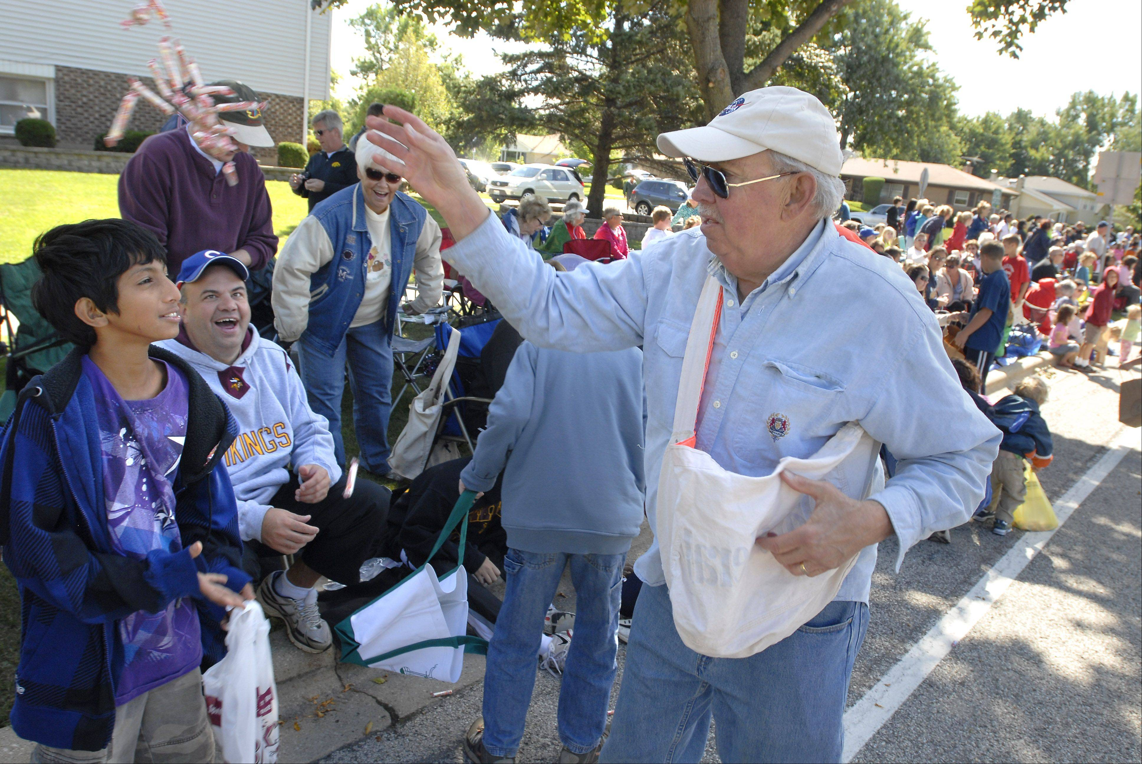 Schaumburg mayor Al Larson tosses candy to viewers along the route Monday at the Septemberfest Parade.