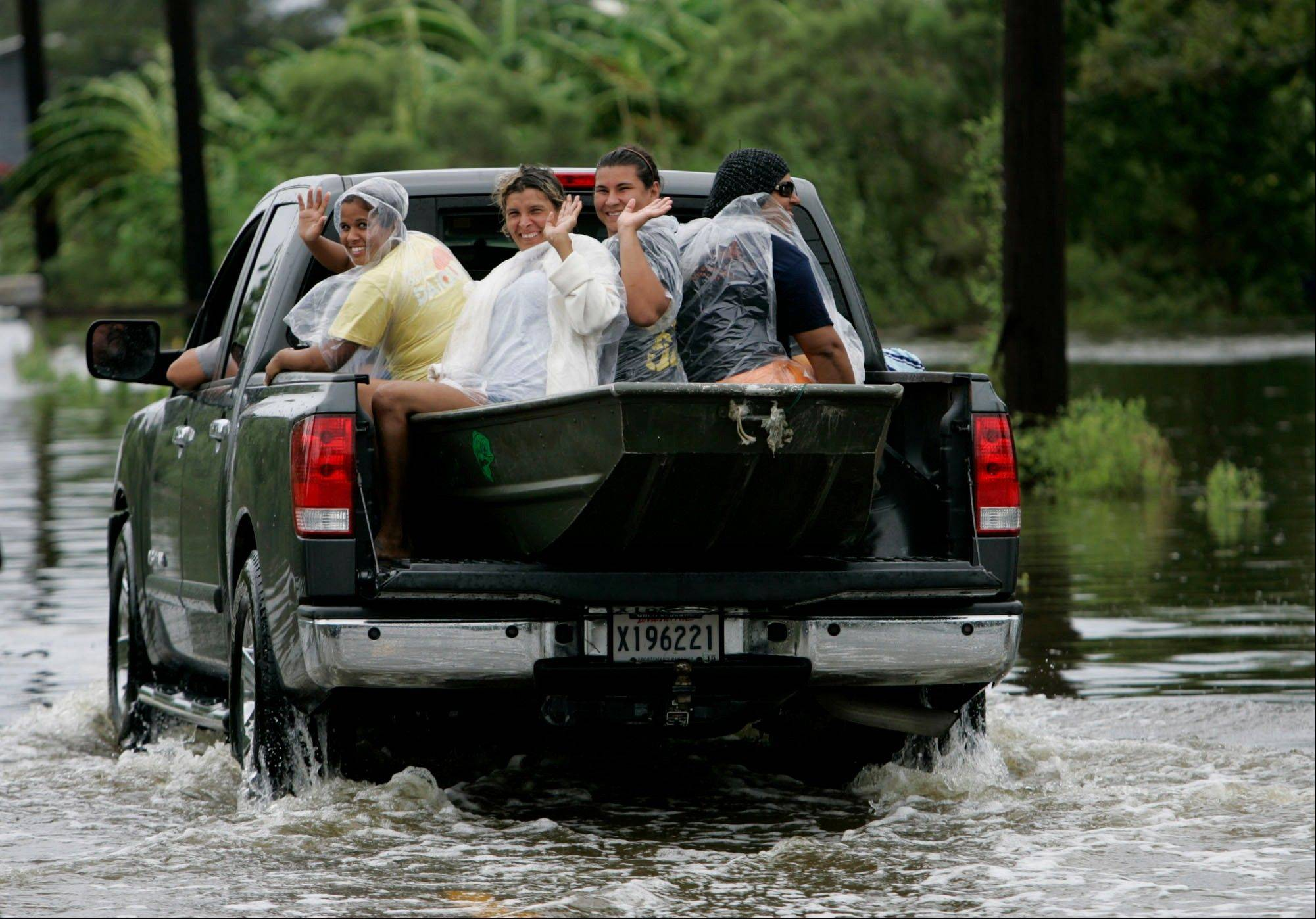 Residents of Dulac, La., ride through floodwater brought on by Tropical Storm Lee Sunday.