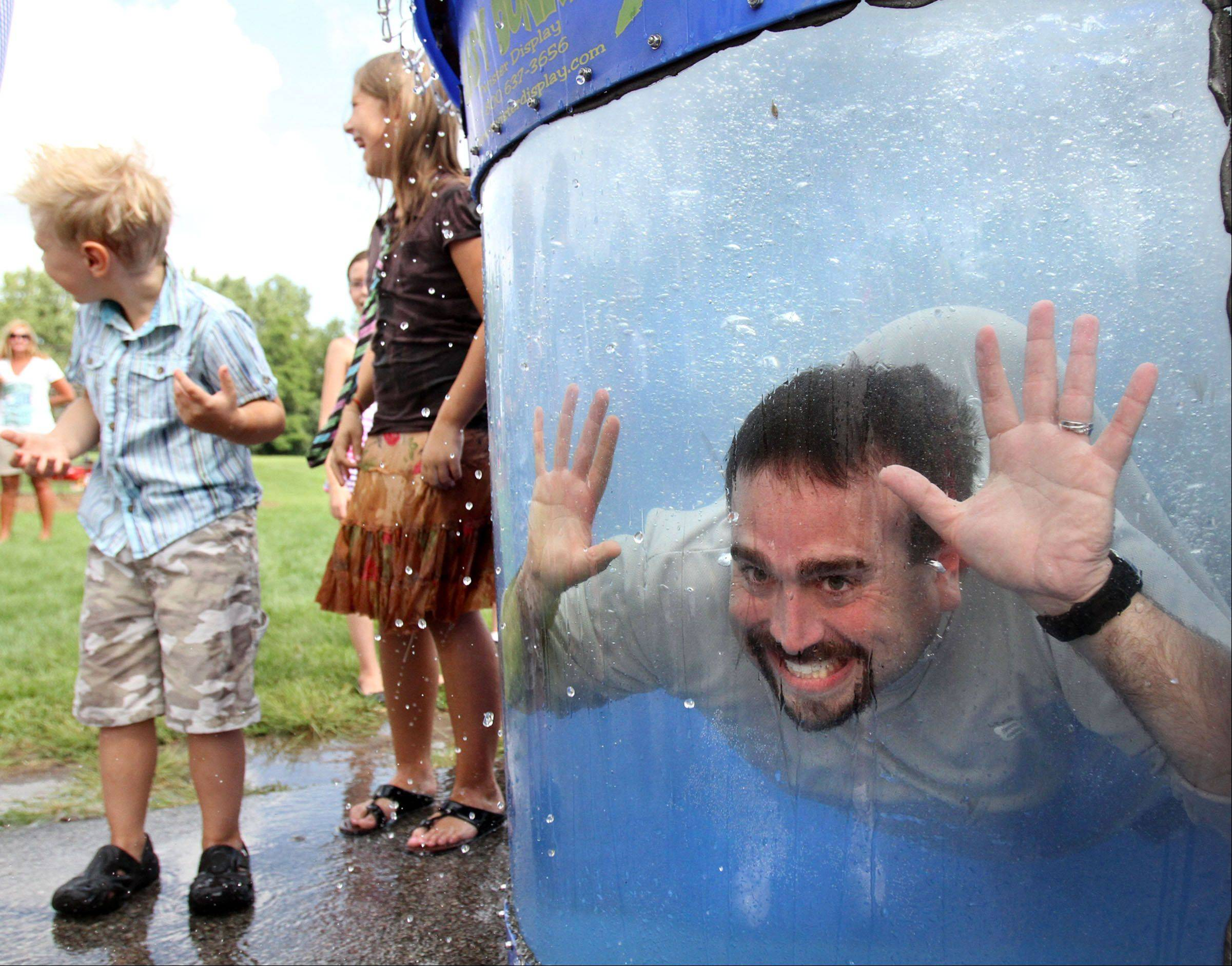 Cameron Shapiro, principal of Seth Paine Elementary School, while underwater in the dunk tank gets a laugh from students including fourth-grader Maja Keska, center, at the school's 50th birthday party held by Lake Zurich Community Unit School District 95 at the school in Lake Zurich on Saturday, August 27th.