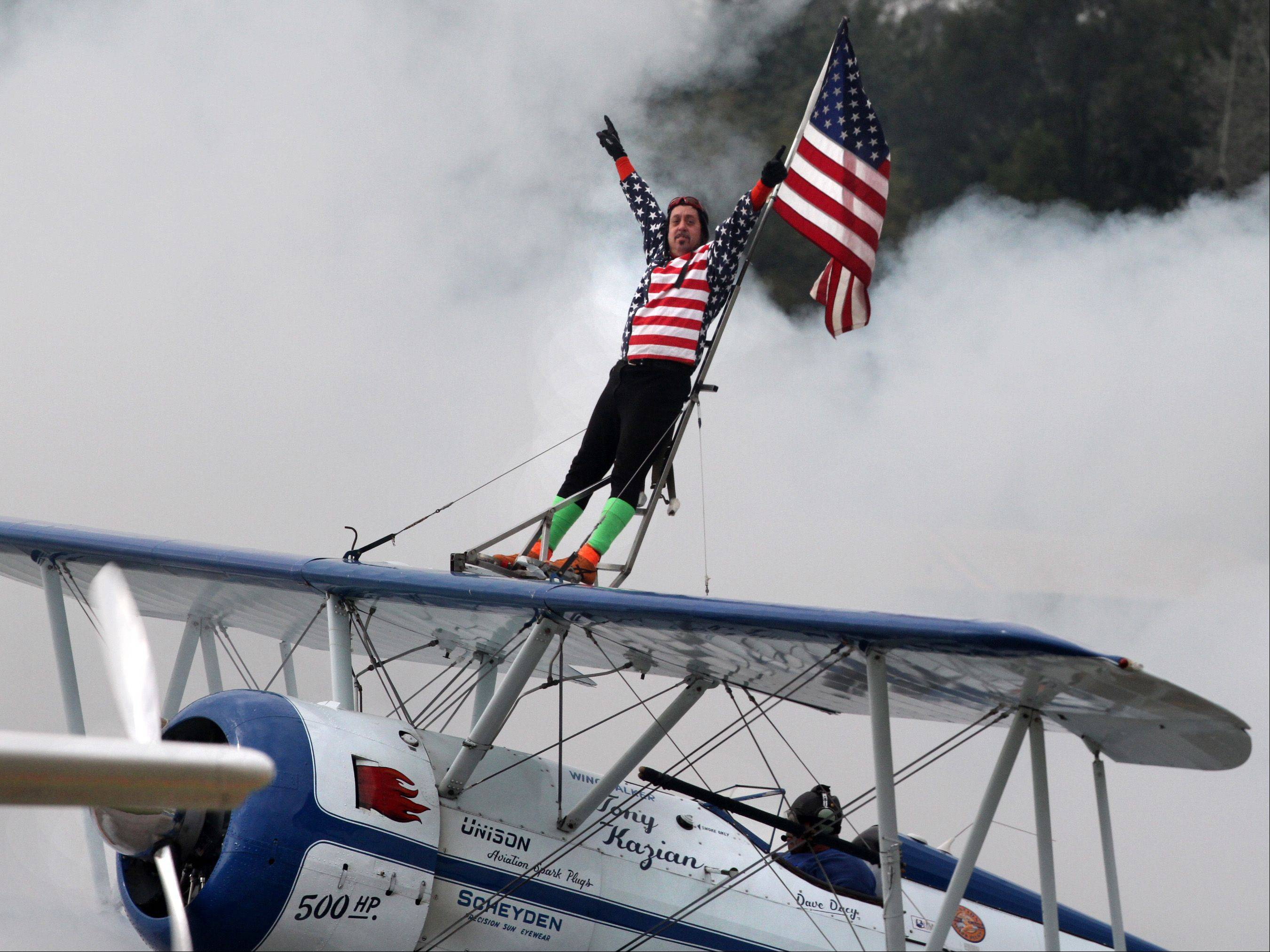 Wingwalker Tony Kazian waves to the crowd during last year's Waukegan Air Show.