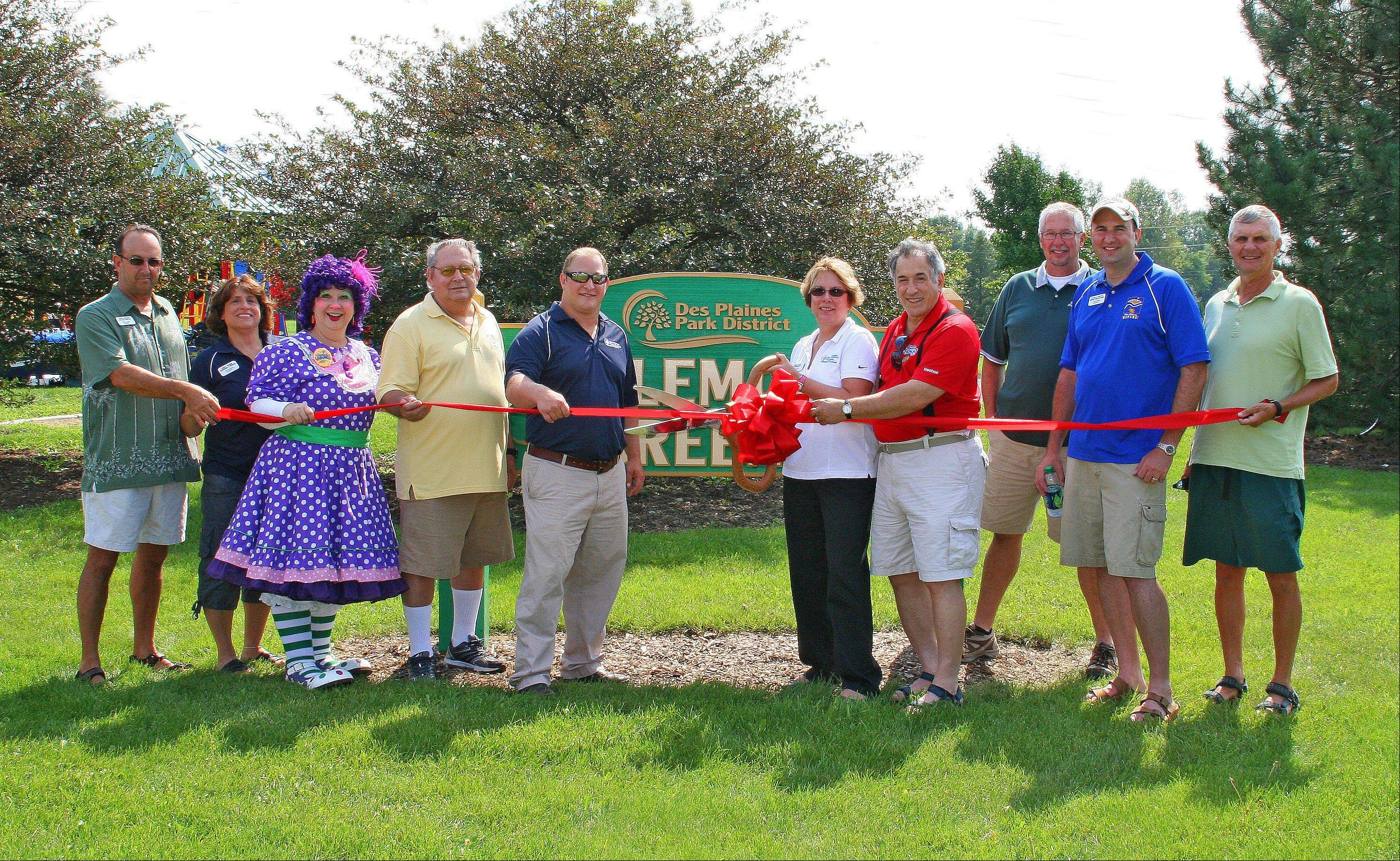 Des Plaines Park District Executive Director John Hecker, left, Superintendent Linda Traina, Jewels the Clown, Mike Lake, Board Commissioner Joe Weber, Board President Jana Bishop Haas, Des Plaines Mayor Martin Moylan, Superintendent Paul Cathey, Superintendent Don Miletic, and 7th Ward Alderman Dan W. Wilson took part in the ribbon-cutting ceremony for Kylemore Greens Park in Des Plaines on Saturday, Aug. 27.