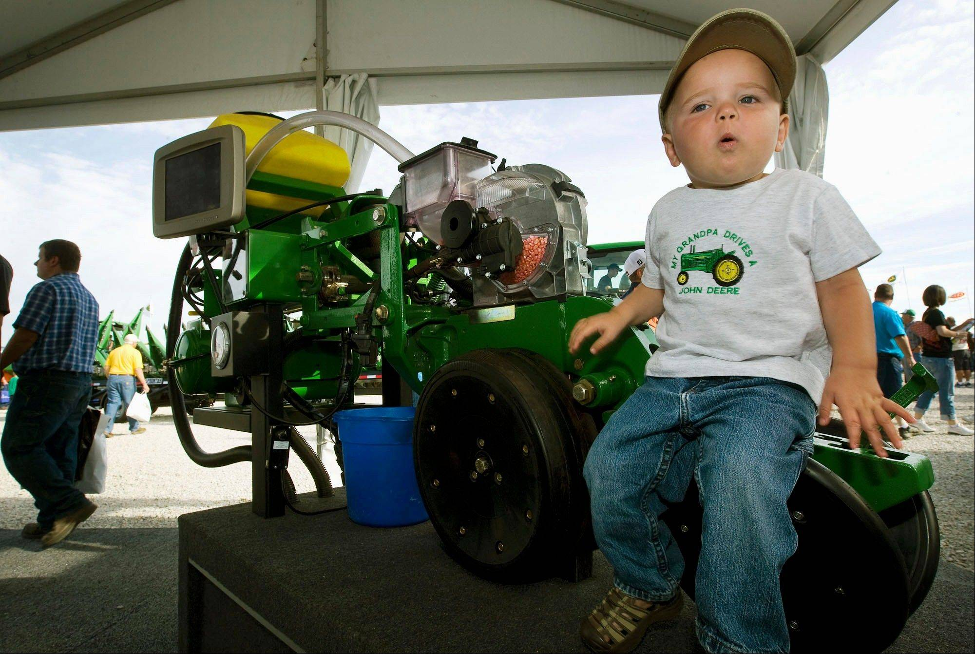 Colten Stundebeck, of Salisbury, Mo., checks out his grandfather John's farm machinery brand under the John Deere tent at the Farm Progress Show in Decatur.