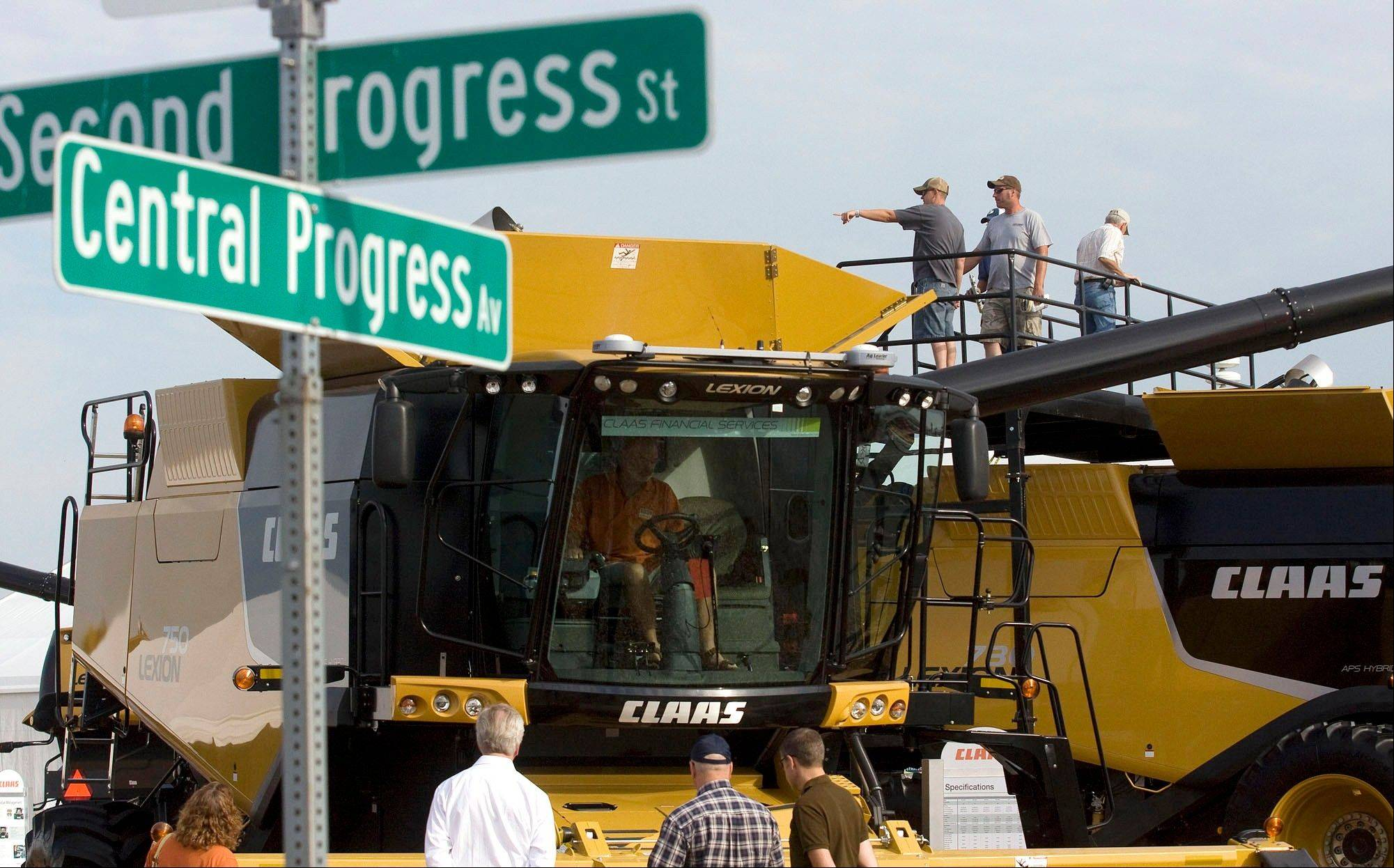 Visitors to the 2011 Farm Progress Show swarm around, in and on top of the Claas Lexon 750 combines.