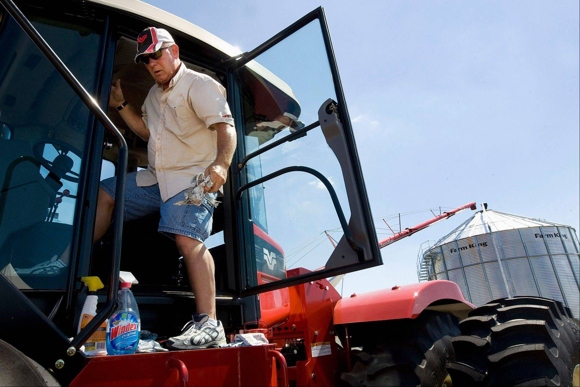 Alan Graff, territorial manager of Winnipeg, Canada-based Buhler Industries, does some last minute cleaning to his Versatile tractor at the 2011 Farm Progress Show.