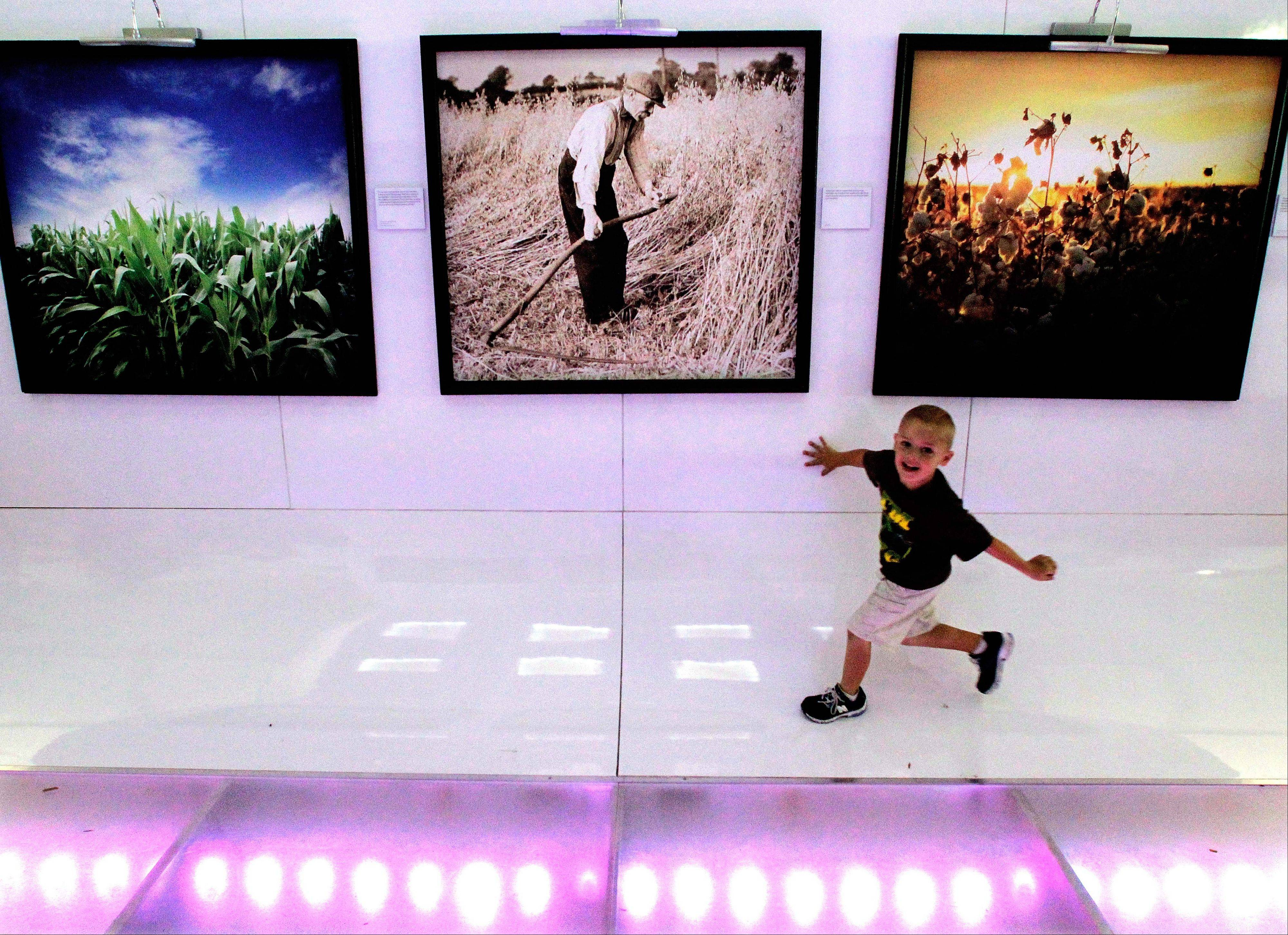 "Kase Kopalz, 6, of Danville, Ill., enjoys the ""History of the American Farmer"" exhibit in the Bayer Corporate Science tent at the Farm Progress Show in Decatur."