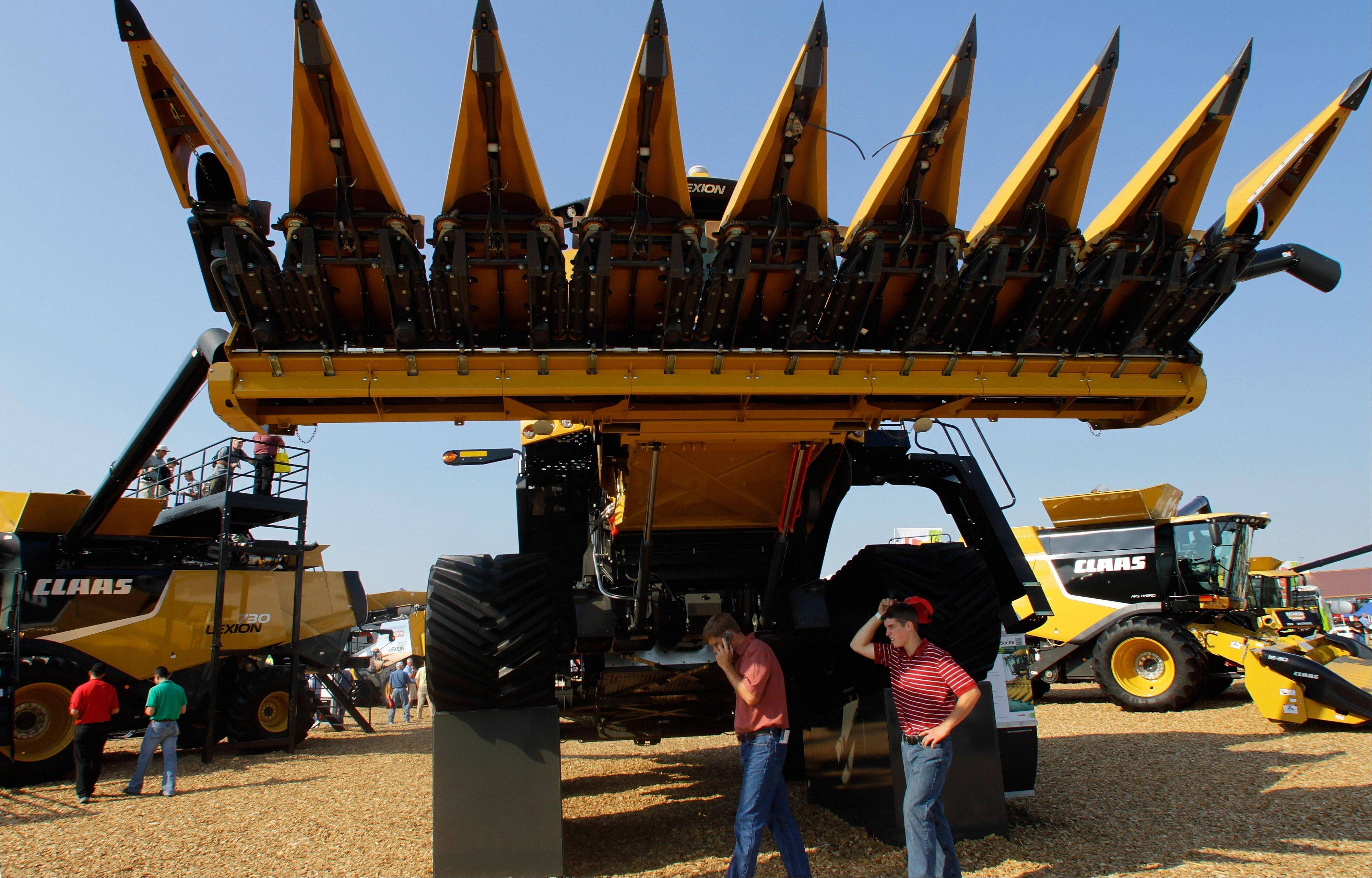 Farmers and visitors walk under a CLAAS combine during the Farm Progress Show in Decatur.