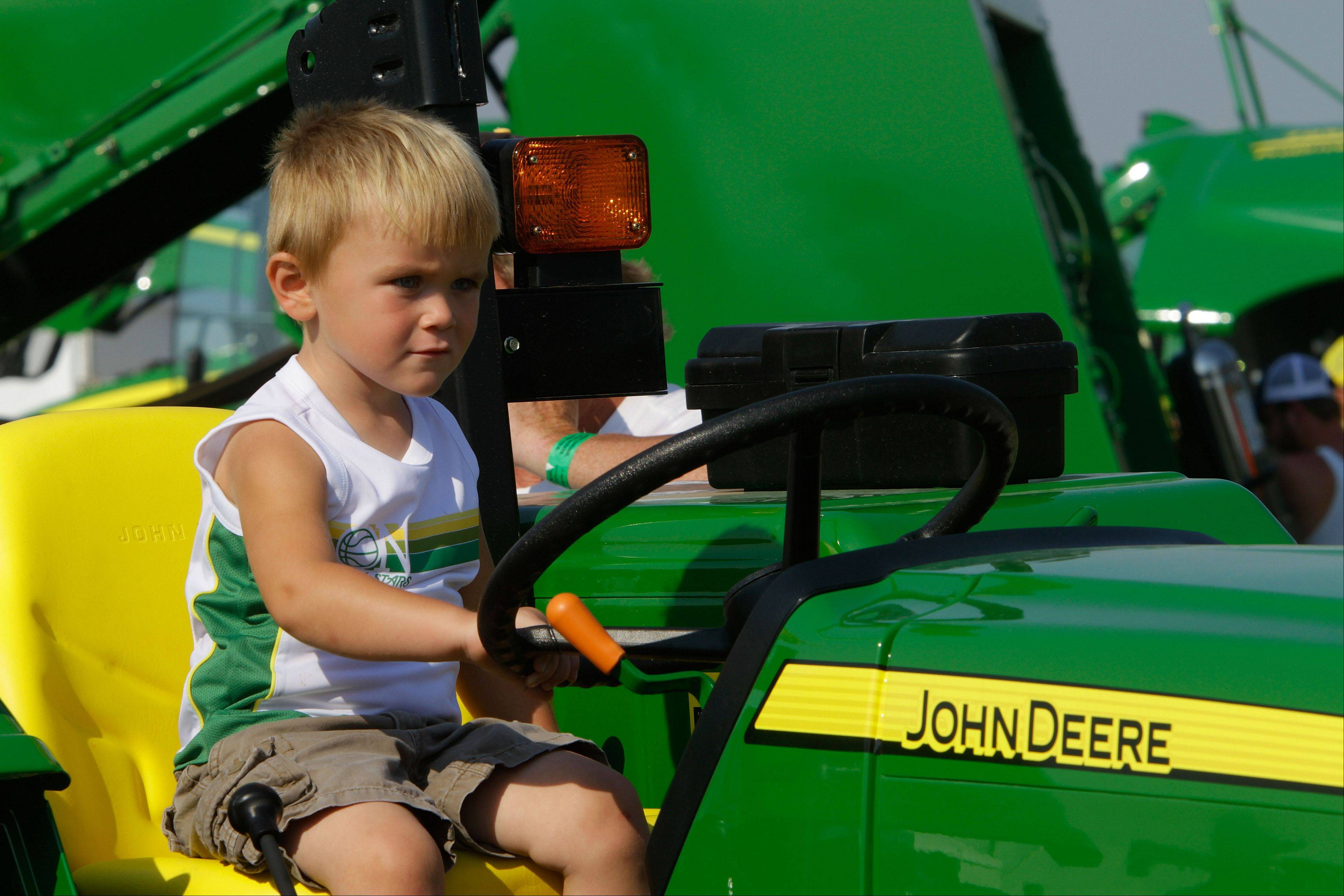 Eathan Beccue of Effingham, Ill., enjoys the John Deere tractor exhibits during the Farm Progress Show in Decatur.