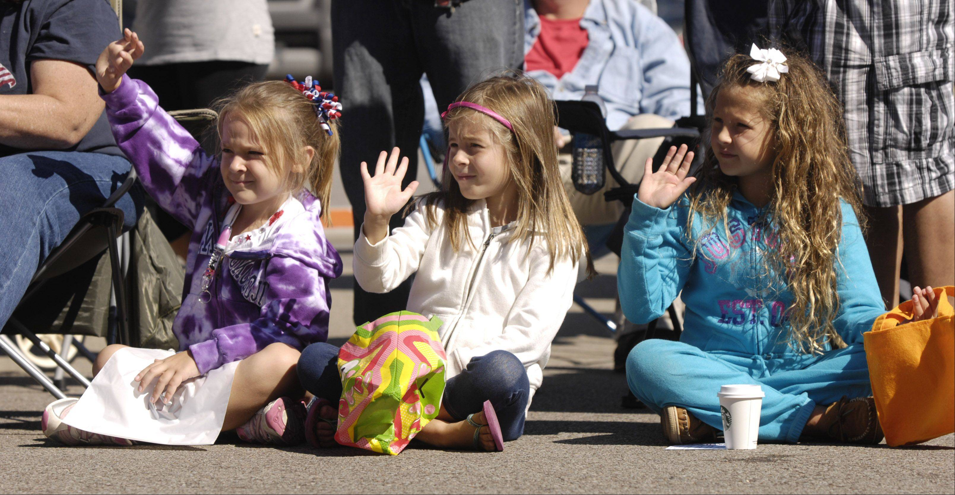 Delaney Miller, 6, Autumn Denson, 6, and Masey Danker, 7, wave as floats in Naperville's Last Fling Labor Day parade pass by.