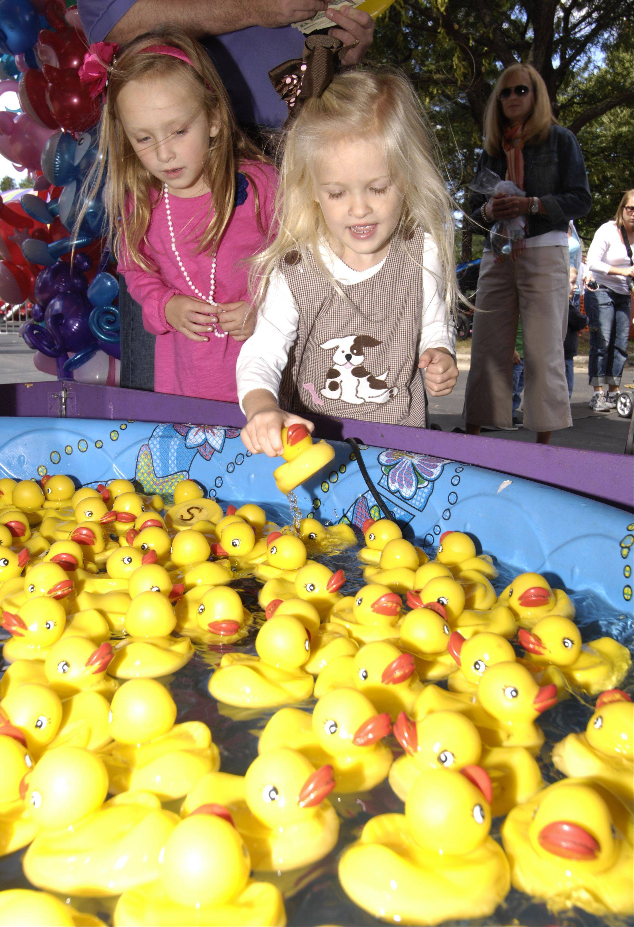 Ava and Amelia Schlappy of Naperville pick ducks to win a prize during the Last Fling carnival in Naperville.