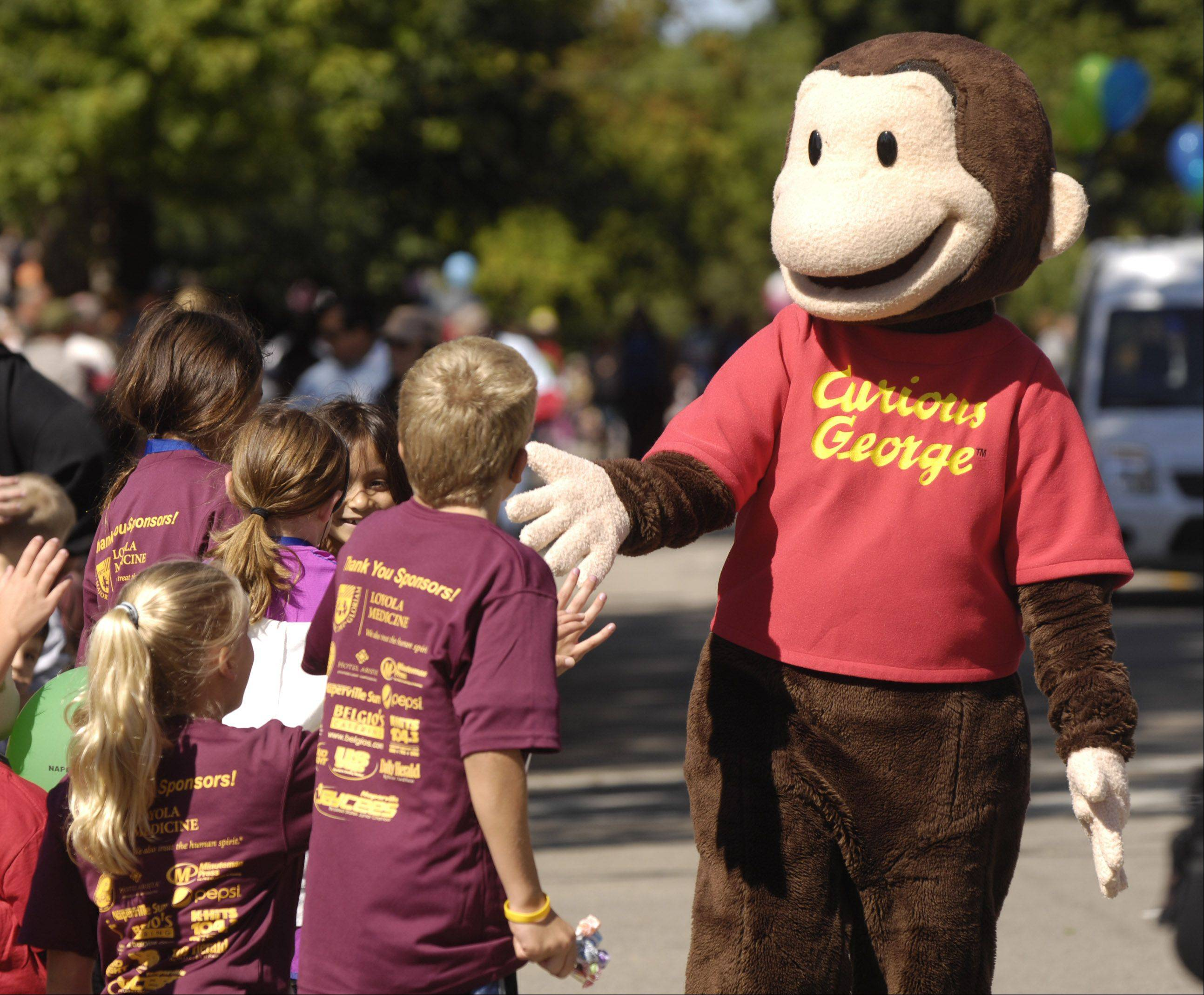 Children's book character Curious George shakes hands with kids along the parade route in Naperville.