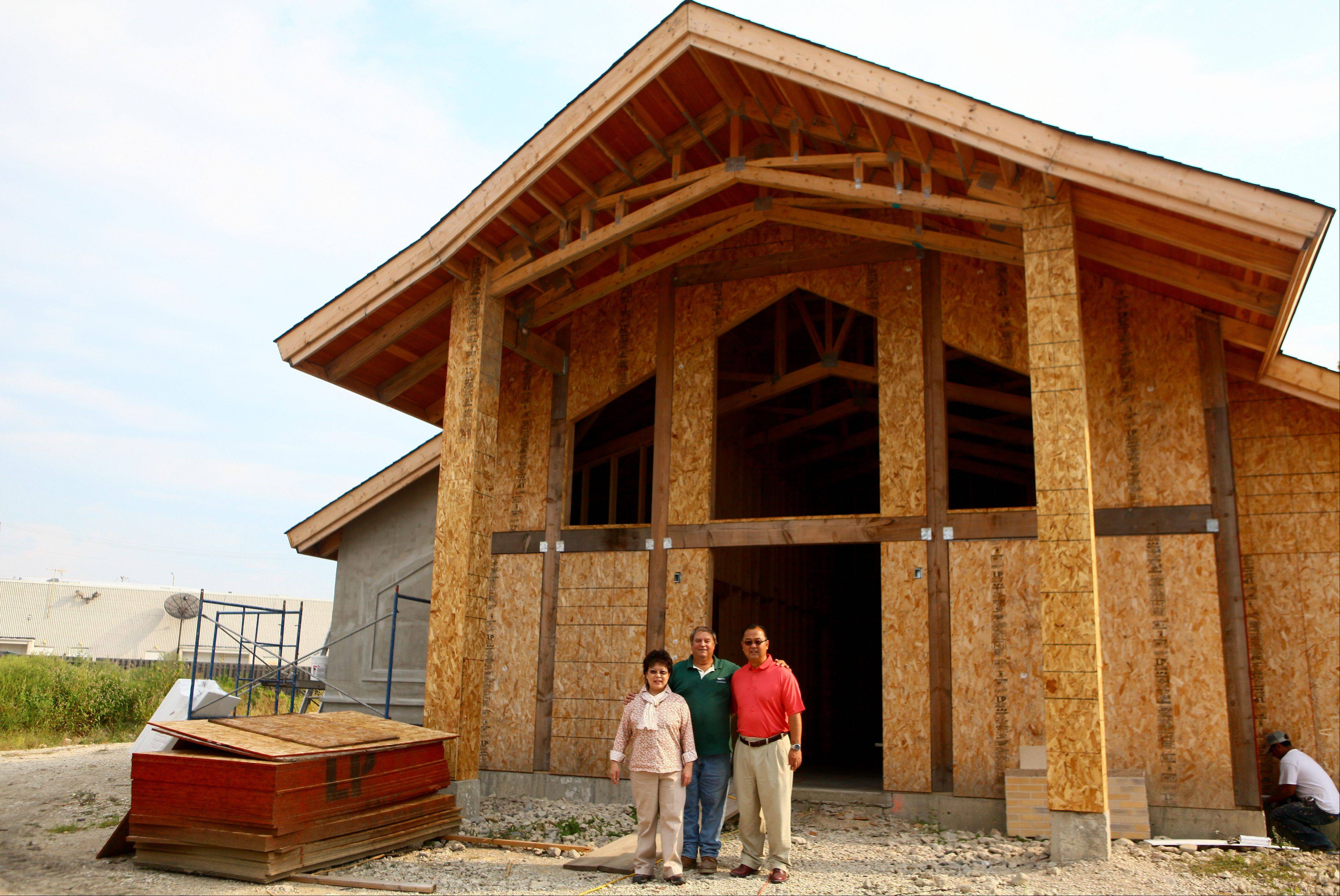 From left, Keiko Kobari, music evangelist, Larry Antemann, contractor, and the Rev. Yugo Kobari stand in front of the new Chicago Japanese Mission Church, under construction at 24 E. Seegers Road in Arlington Heights.