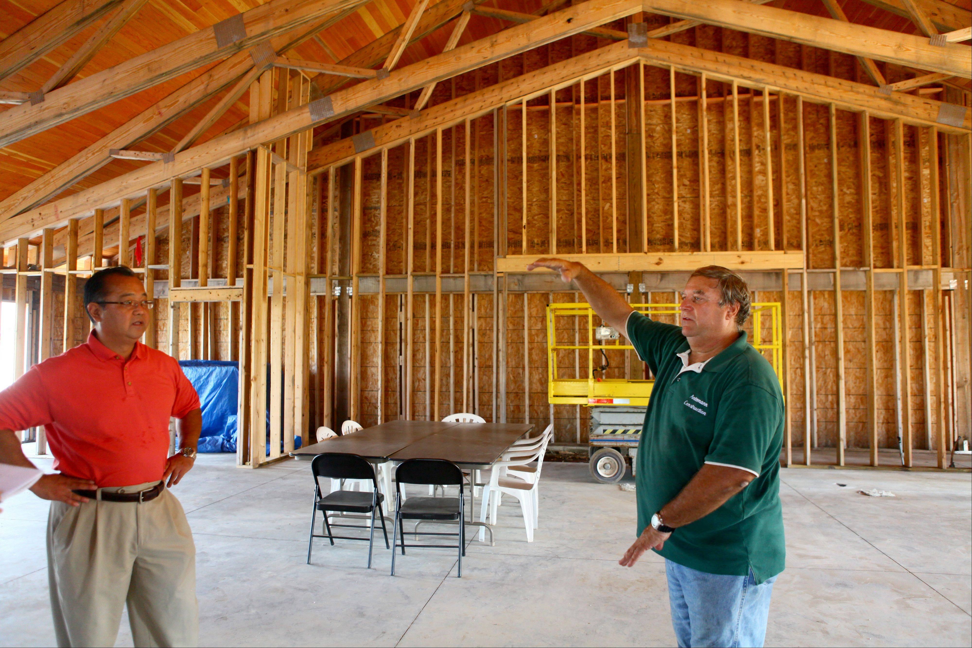 Contractor Larry Antemann, right, talks with the Rev. Yugo Kobari about the new church under construction near Mitsuwa Marketplace in Arlington Heights.