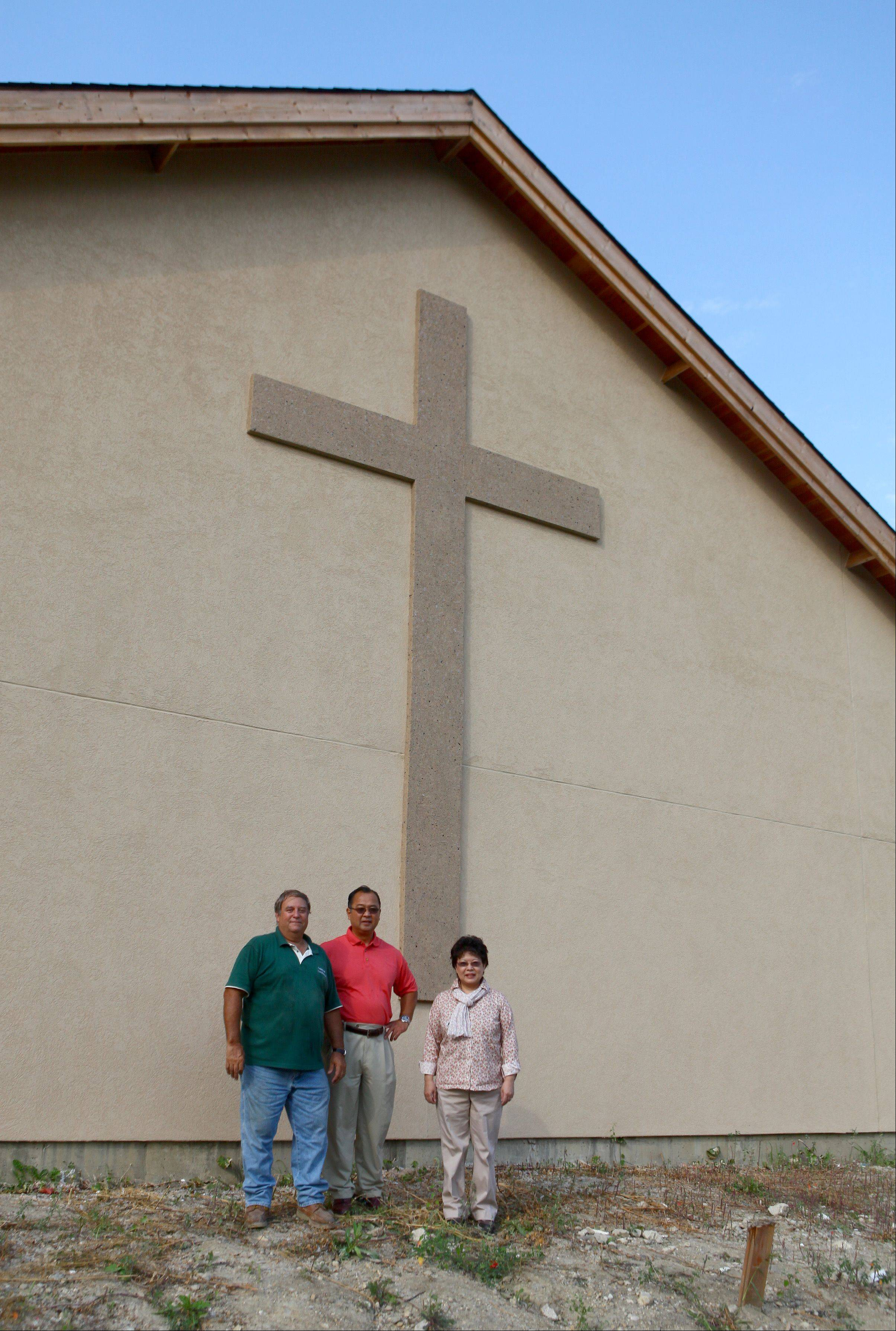 Contractor Larry Antemann, the Rev. Yugo Kobari and Keiko Kobari are proud of the cross just installed in the church under construction the new Chicago Japanese Mission Church in Arlington Heights.