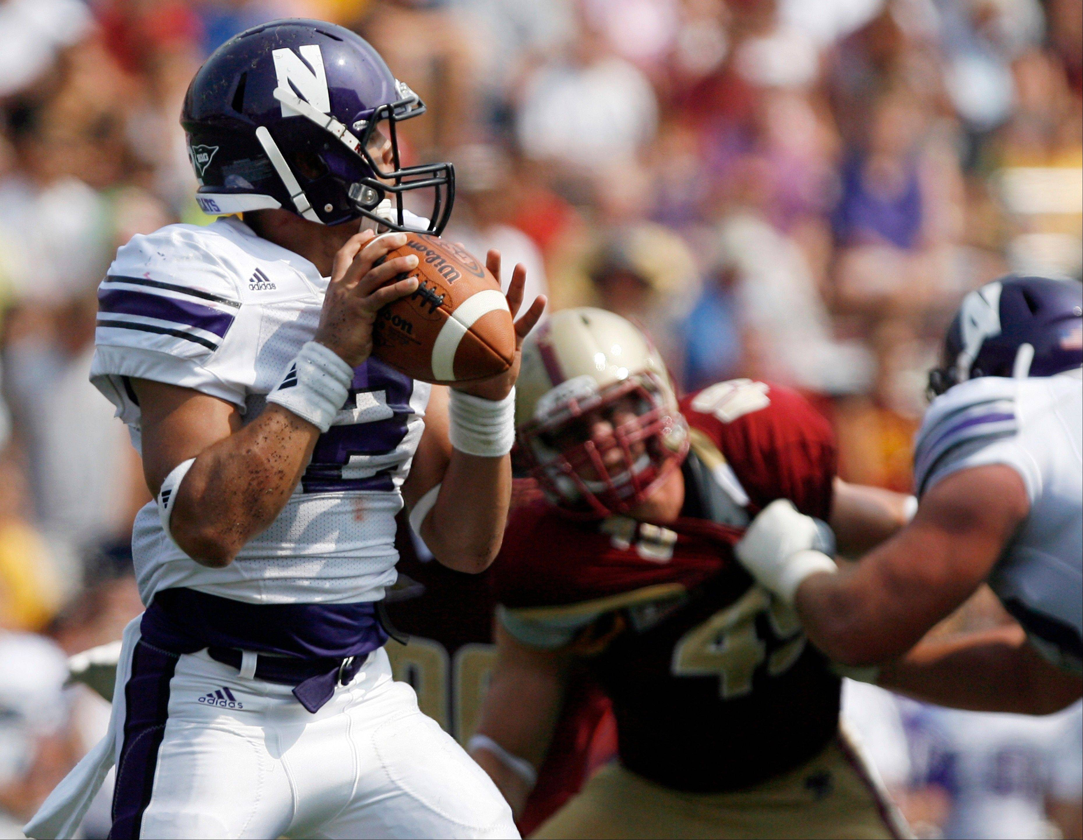 Northwestern quarterback Kain Colter (2) gets some blocking help as he looks to pass during the second half of an NCAA college football game Saturday against Boston College in Boston.