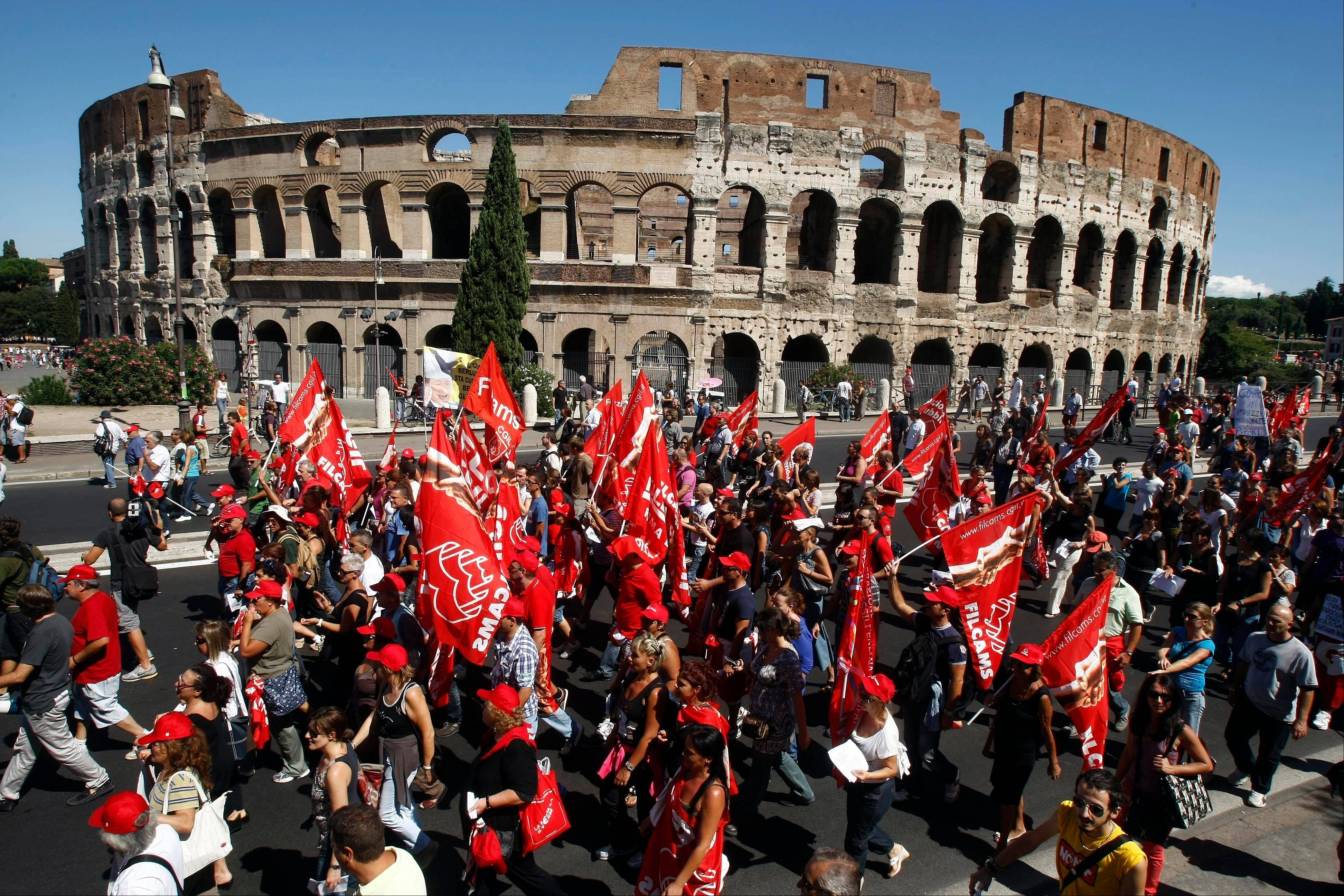 Demonstrators march past the Colosseum during a general strike in Rome on Tuesday. With Silvio Berlusconi's government under increasing pressure to produce credible measures to balance the budget, a strike by Italy's largest labor union against an austerity package shut down air, land and sea transport, stalled manufacturing and curtailed government services throughout the country on Tuesday.