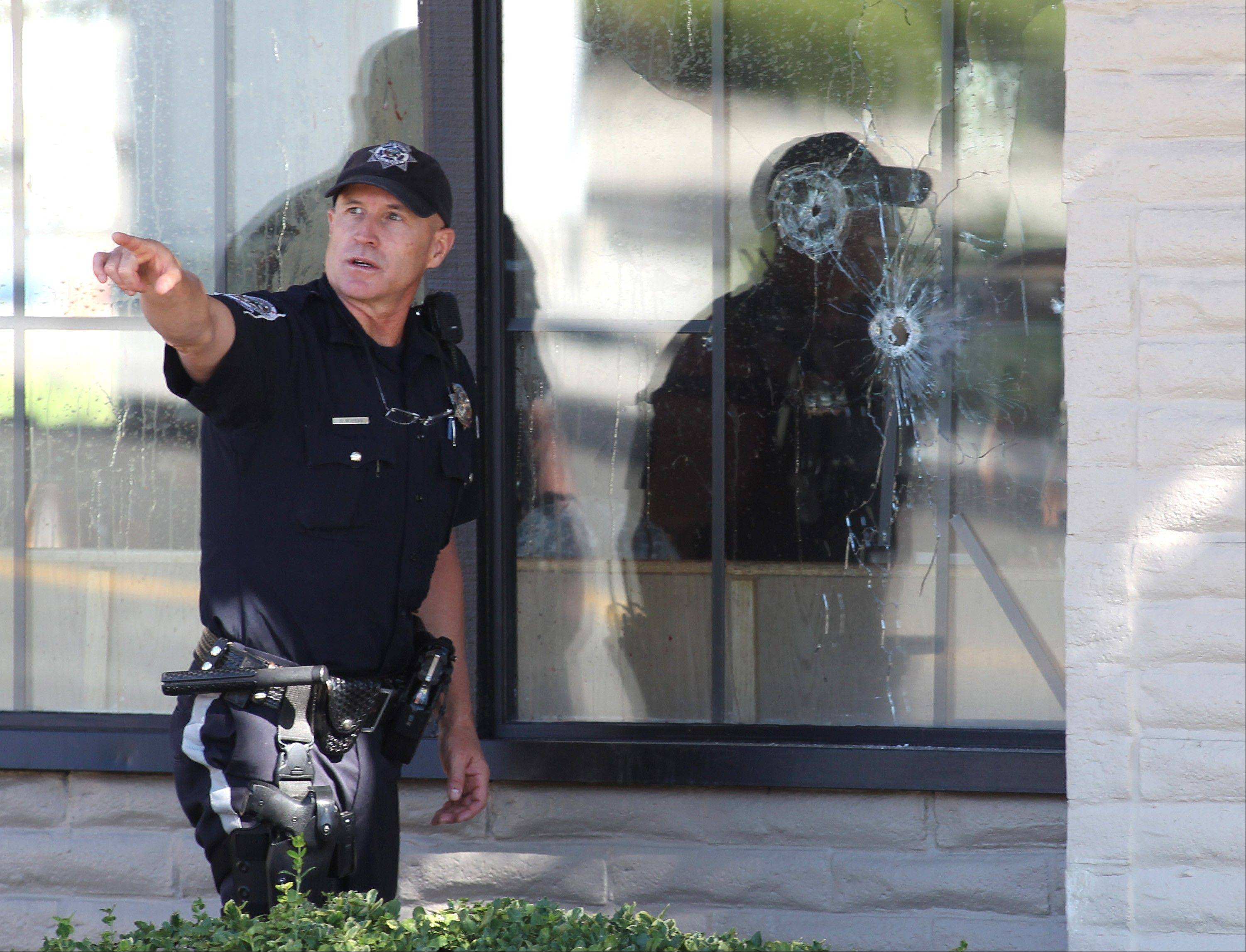 With bullet holes seen in a window, officers look for evidence at the scene of a shooting at an IHOP restaurant in Carson City, Nev., Tuesday.