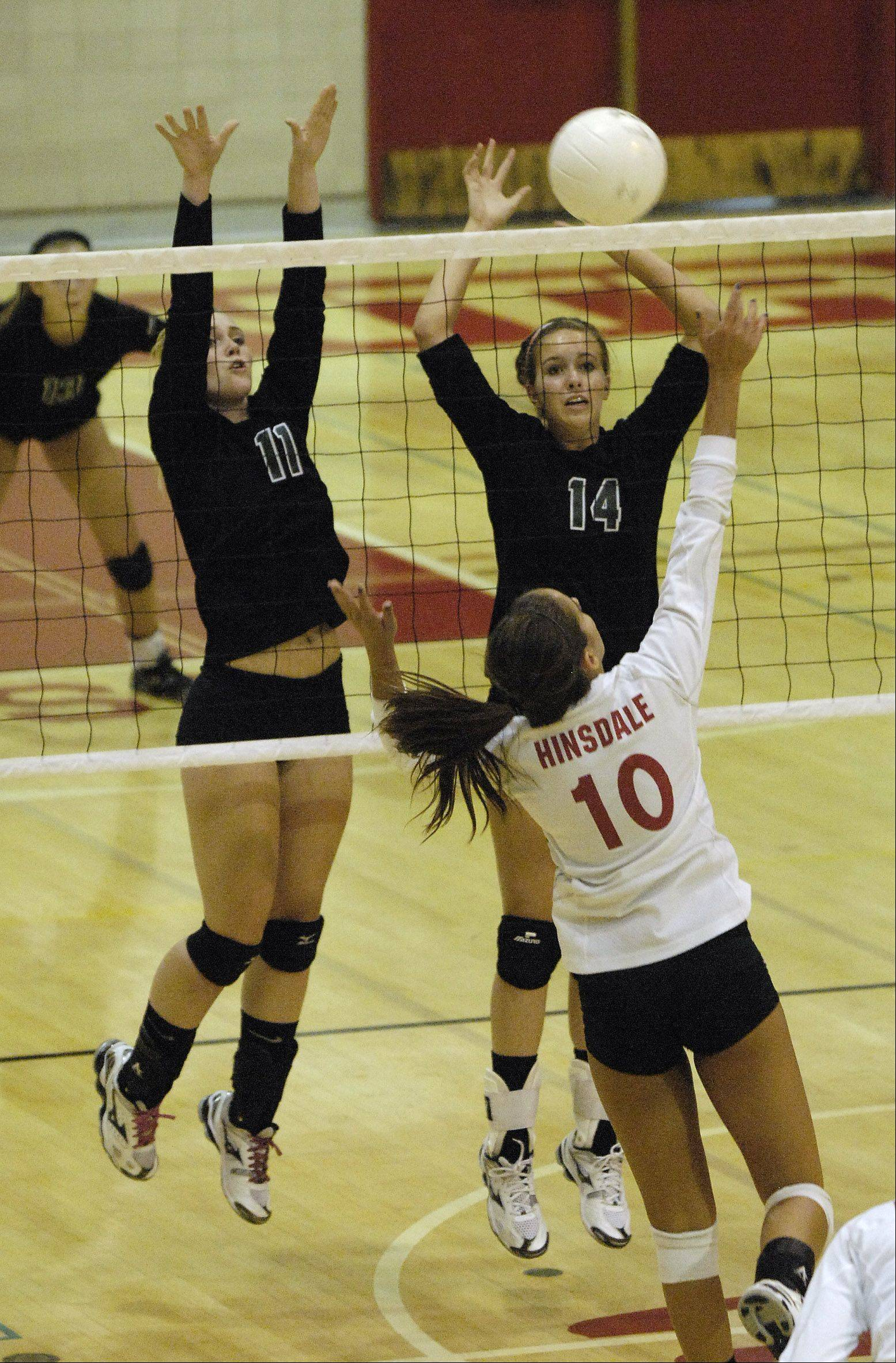 Caleigh Ryan and Katie Ball of Glenbard West look to block a shot by Katie Grabowski of Hinsdale Central during girls varsity volleyball action in Hinsdale.