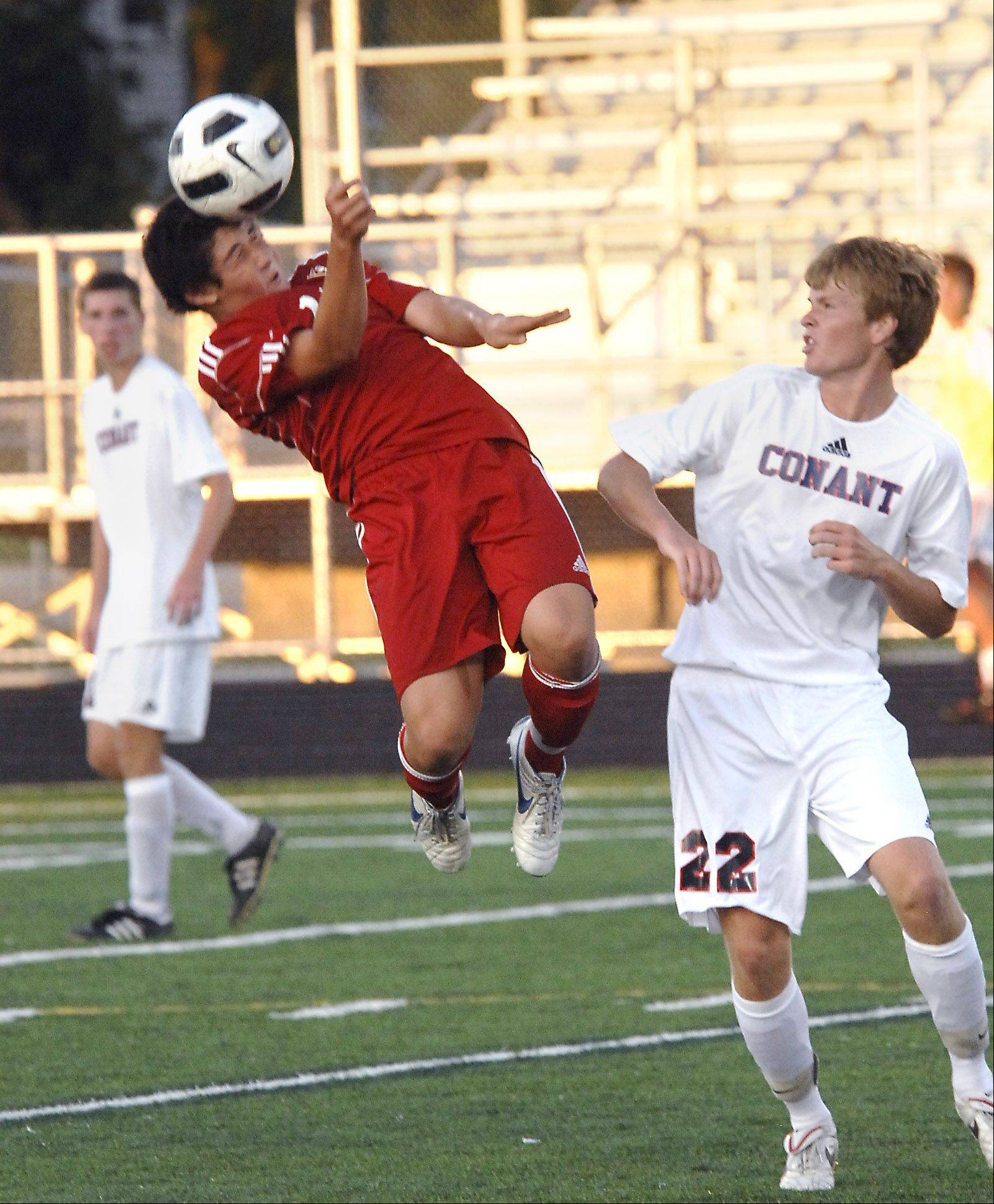 Palatine�s Tim Murphy, 10, gets off a header against Conant�s Jamie Blonde Monday at Conant.