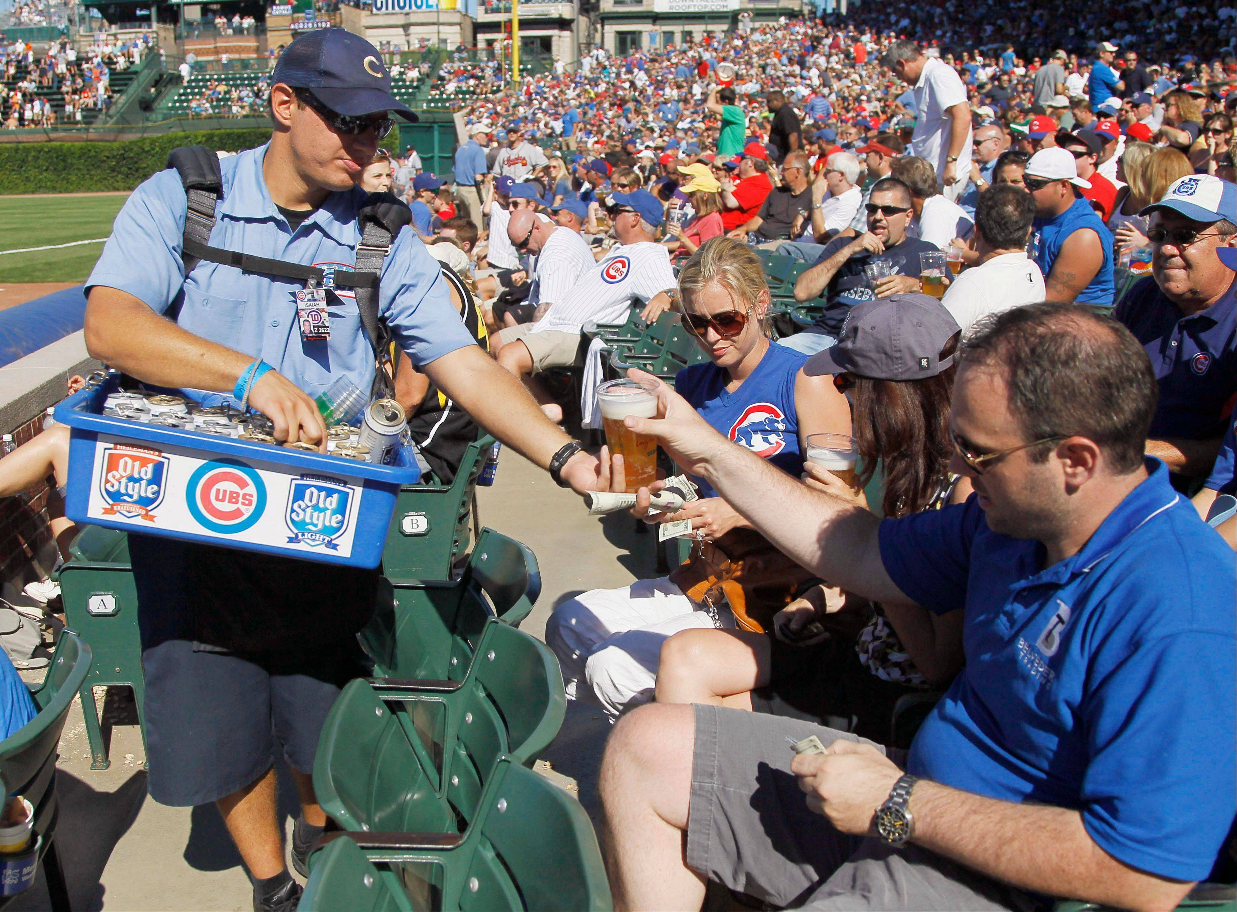 A vendor sells an Old Style beer to a fan during a Cubs game at Wrigley Field. Pabst Brewing Company threatened earlier this year to pull Old Style from the ballpark, but on Wednesday the Cubs and Pabst announced a deal.