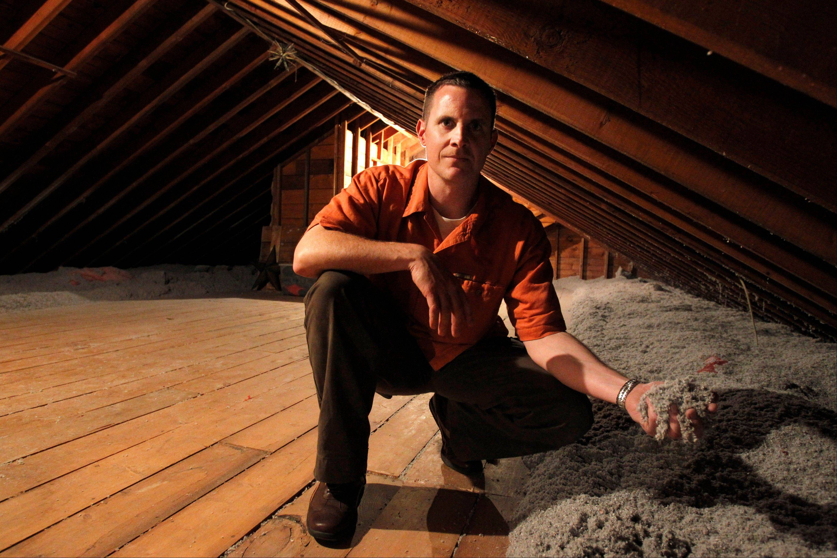 Stephen Botehlo, of Westwood, Mass., holds cellulose insulation in the attic of his home. Botehlo installed the cellulose insulation as an energy saving measure. Associated Press